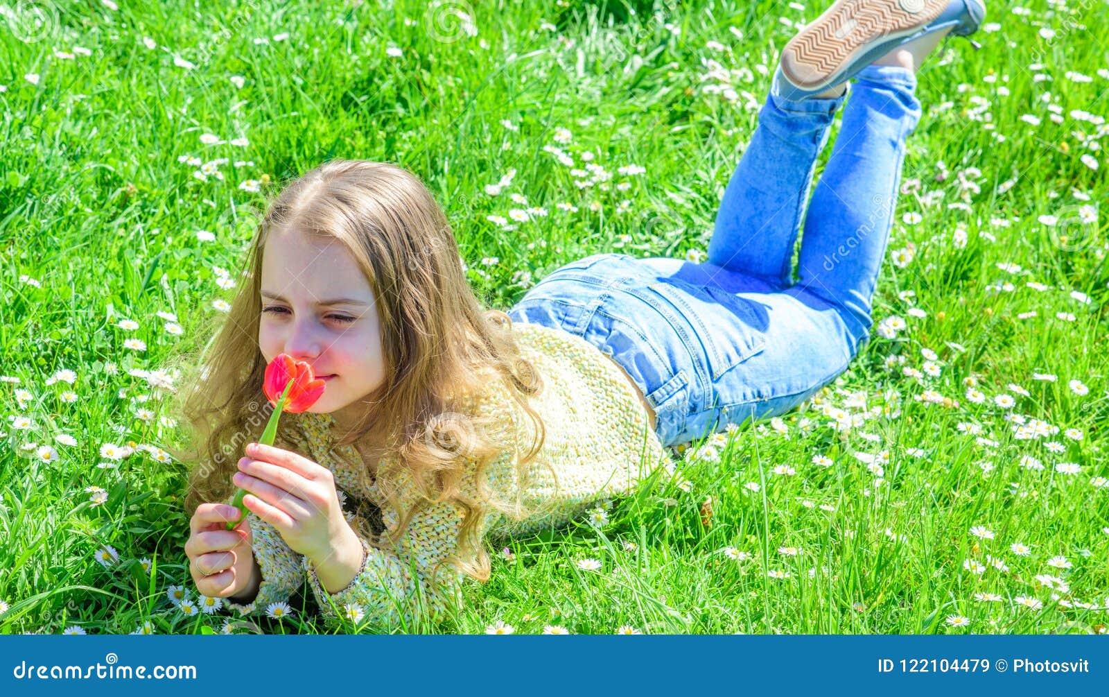 El niño disfruta de la fragancia del tulipán mientras que miente en el prado Concepto de la alergia Muchacha con el pelo largo qu