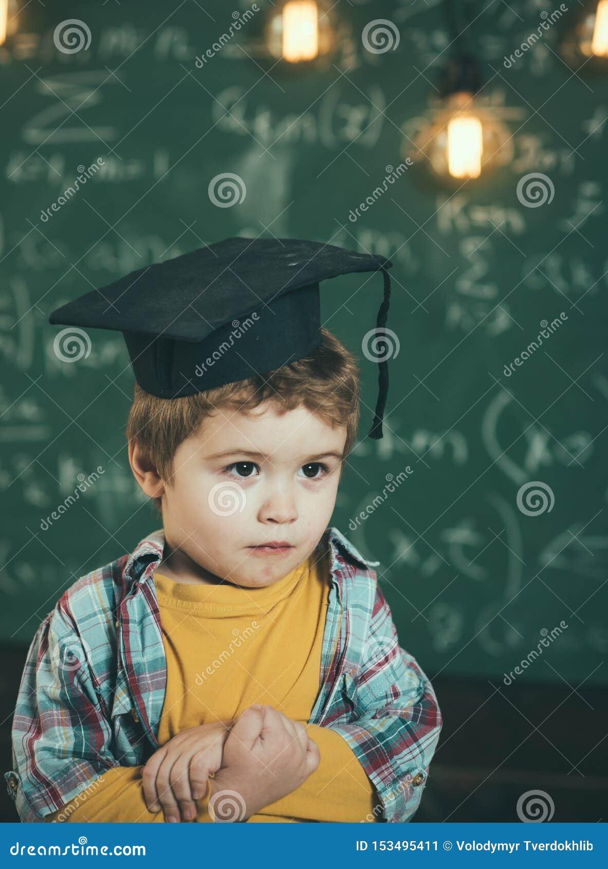 El niño elegante en casquillo graduado en la cara seria, tímida, lleva a cabo las manos cruzadas Niño, preescolar o primer anteri