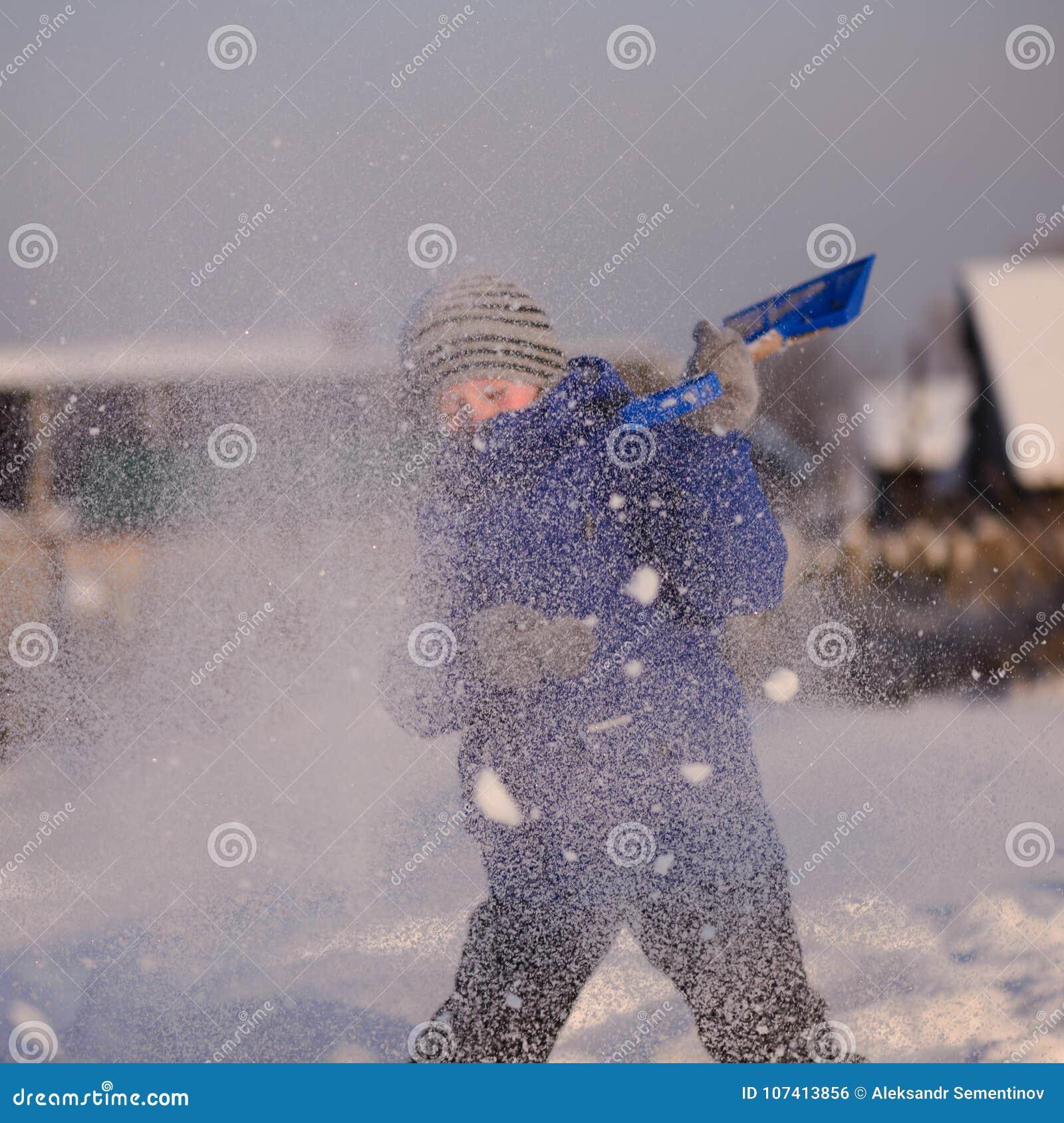 El niño en invierno viste fuera de la ciudad en el fondo de a
