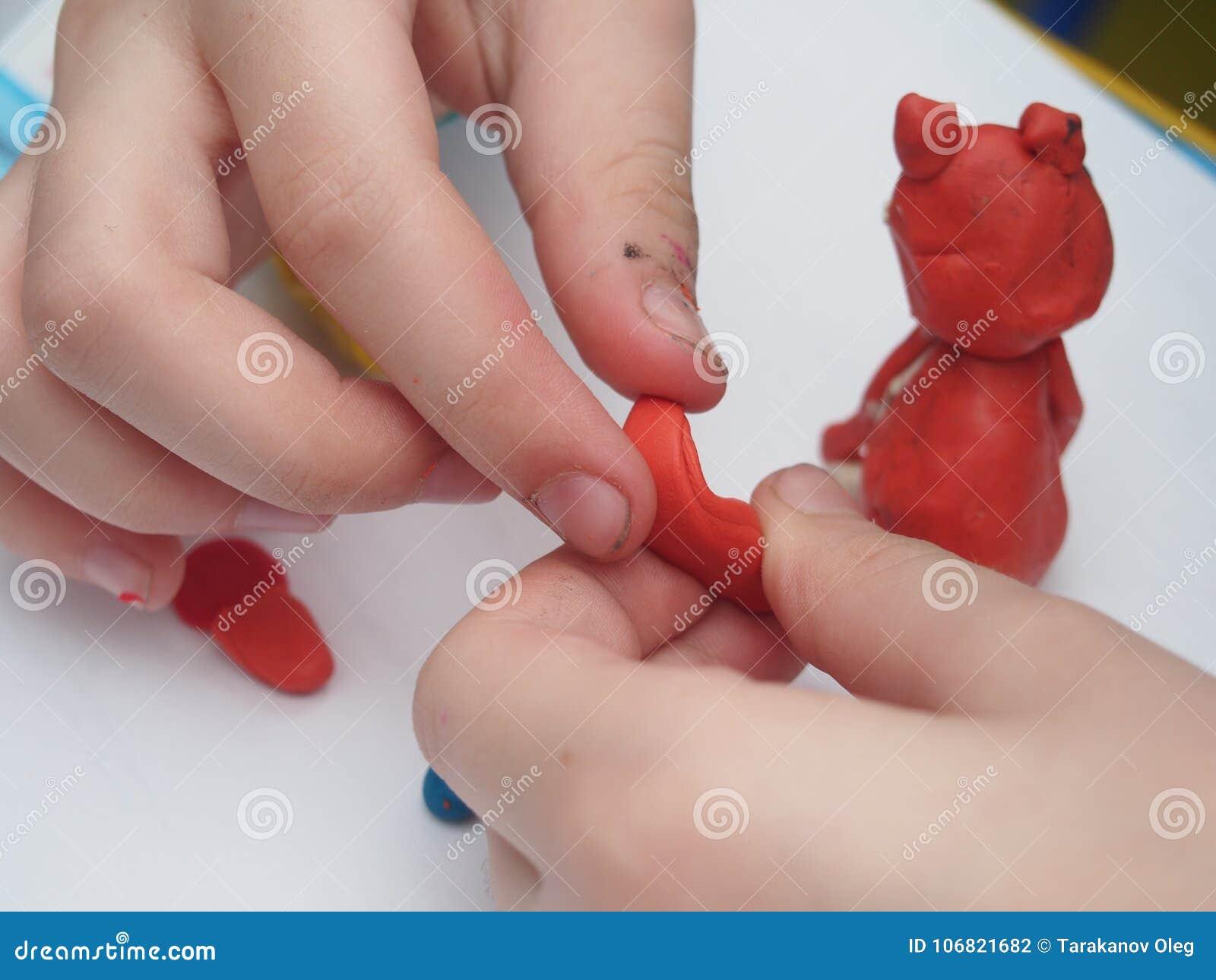 El niño esculpe una figura fuera del plasticine Children& x27; cr artístico de s