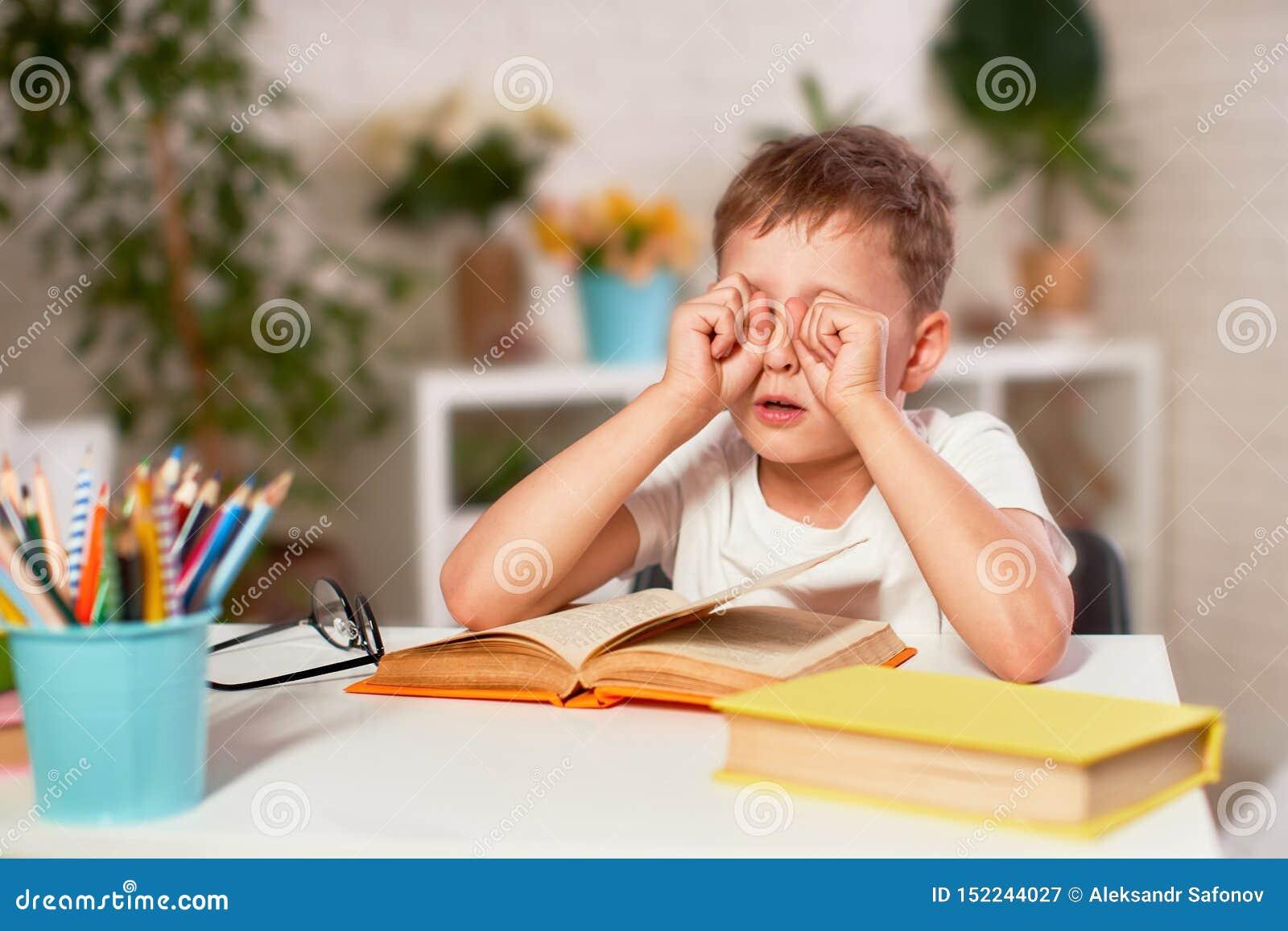 El niño está cansado del aprendizaje el enseñar casero, preparación el muchacho frota sus ojos de los libros y de los libros de t