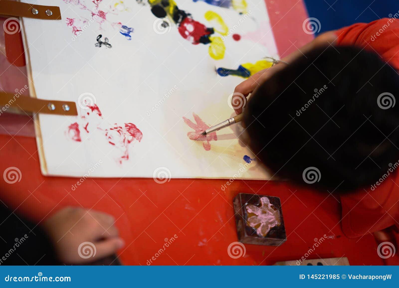 El niño está dibujando las ilustraciones coloreando, visión superior