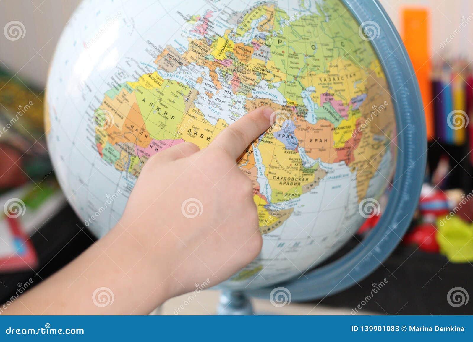El niño está estudiando la geografía Dedo que señala al globo