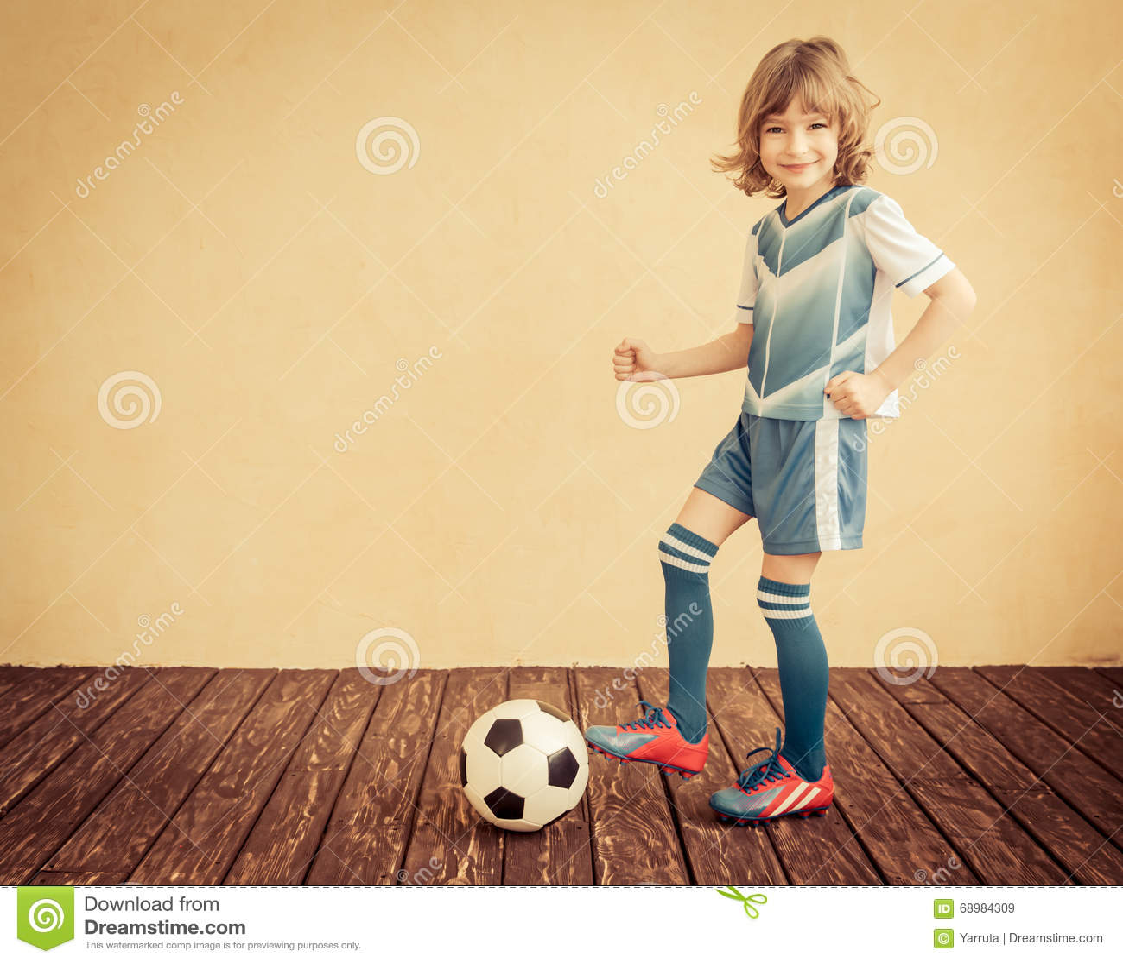 El niño está fingiendo ser jugador de fútbol