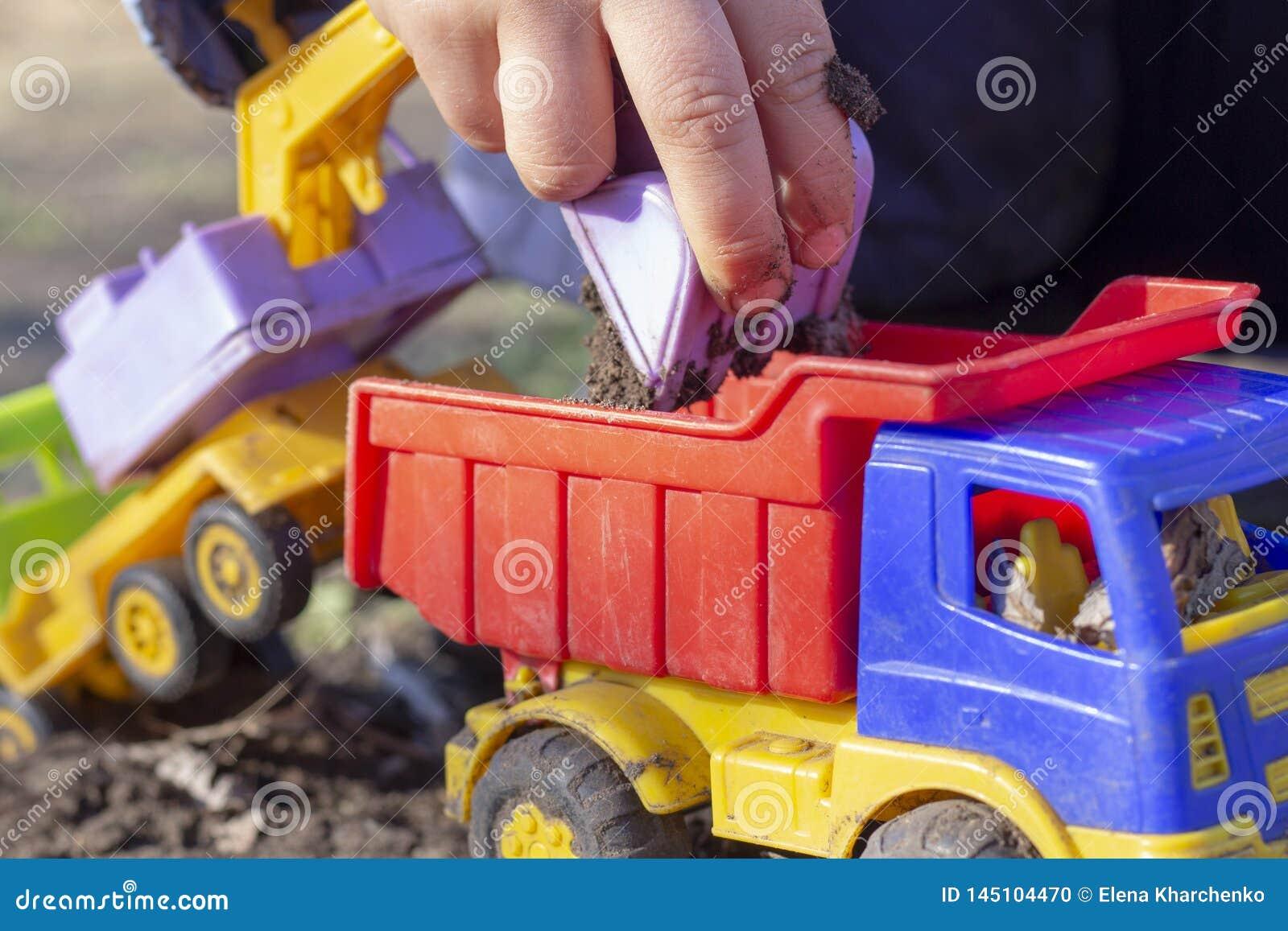 El niño está jugando en la calle con la arena; él carga la tierra en un juguete del camión volquete