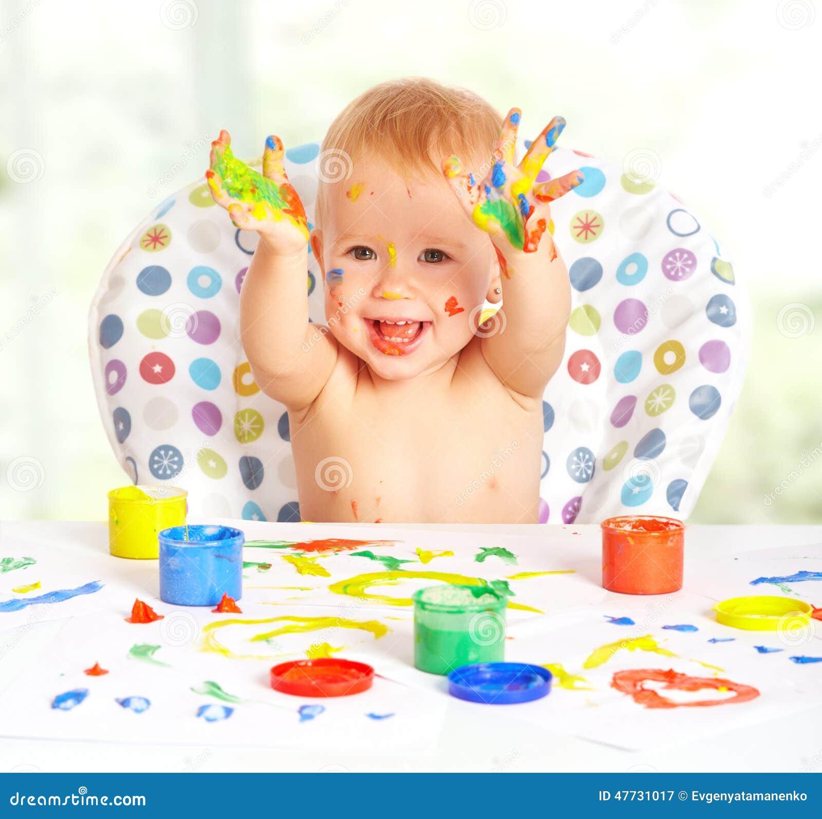 el ni o feliz del beb dibuja con las pinturas coloreadas. Black Bedroom Furniture Sets. Home Design Ideas