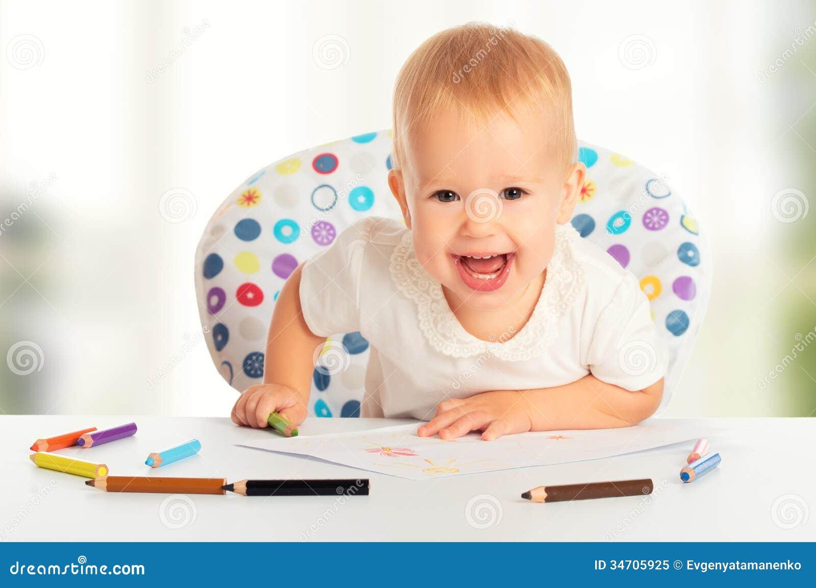 El niño feliz del bebé dibuja con los creyones coloreados de los lápices