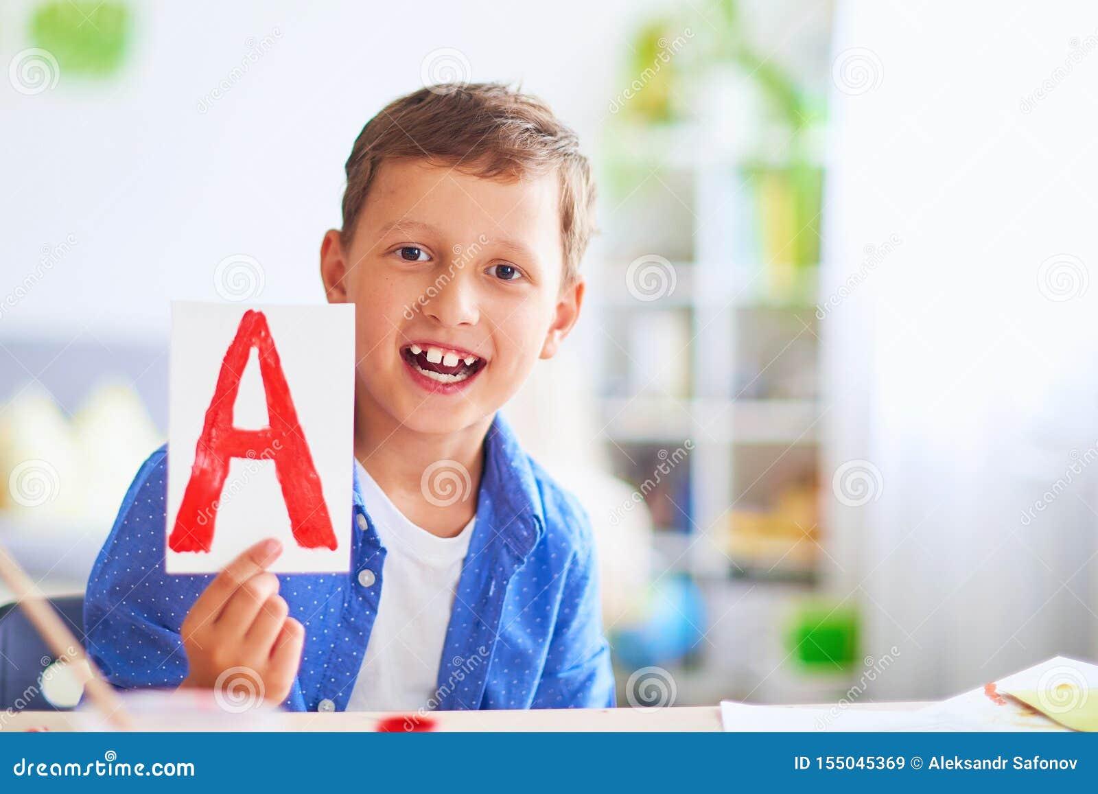 El niño feliz en la tabla con las fuentes de escuela sonríe divertido y aprende el alfabeto de una manera juguetona estudiante po