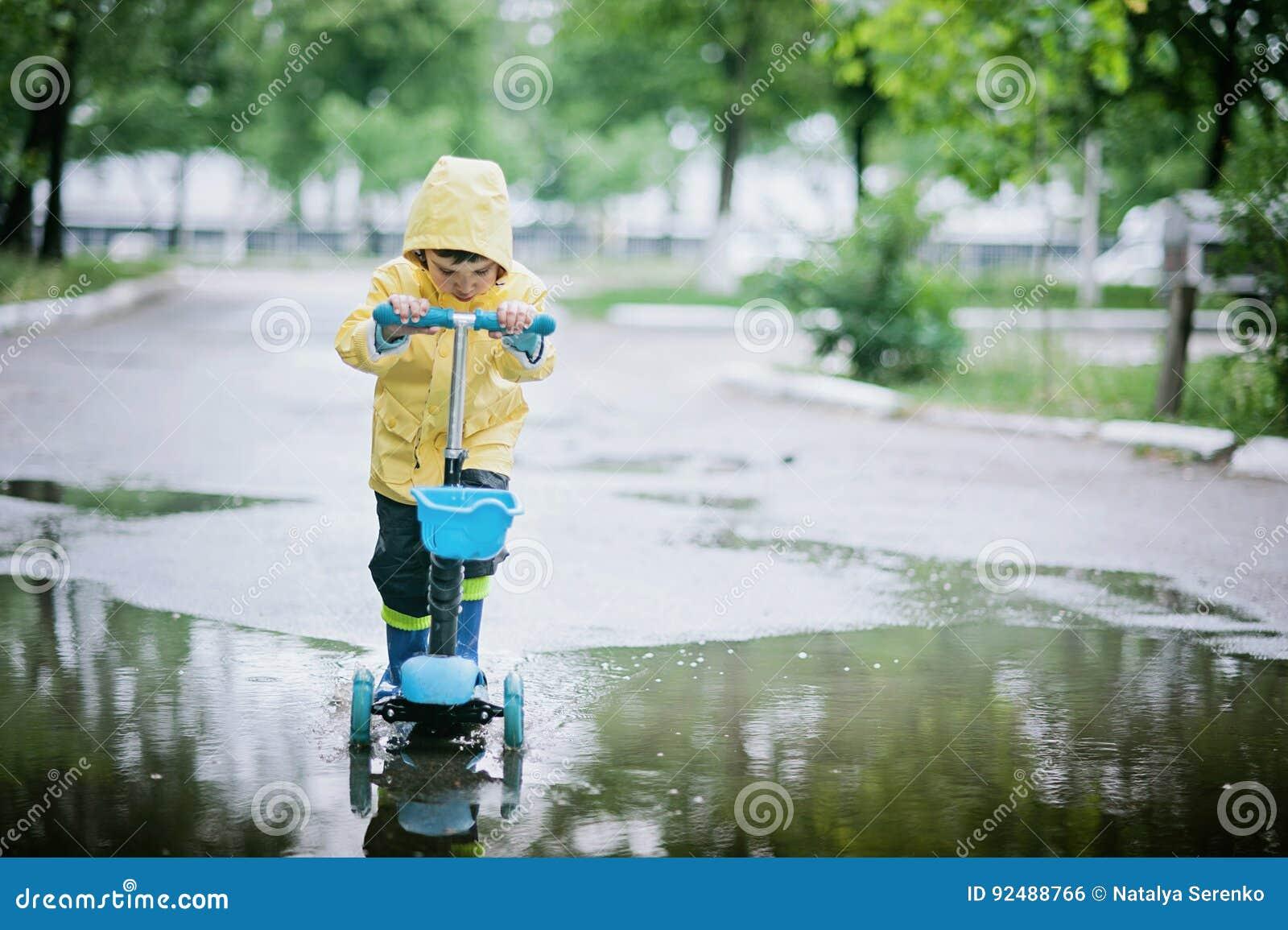 El niño feliz en un impermeable amarillo monta una vespa a través del charco