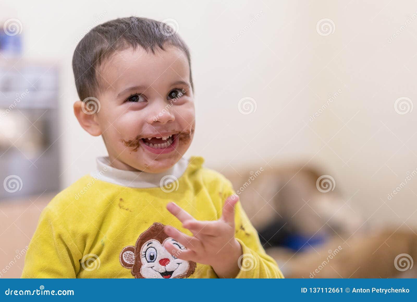 El niño feliz lame una cuchara con el chocolate Muchacho feliz que come la torta de chocolate Bebé divertido que come el chocolat