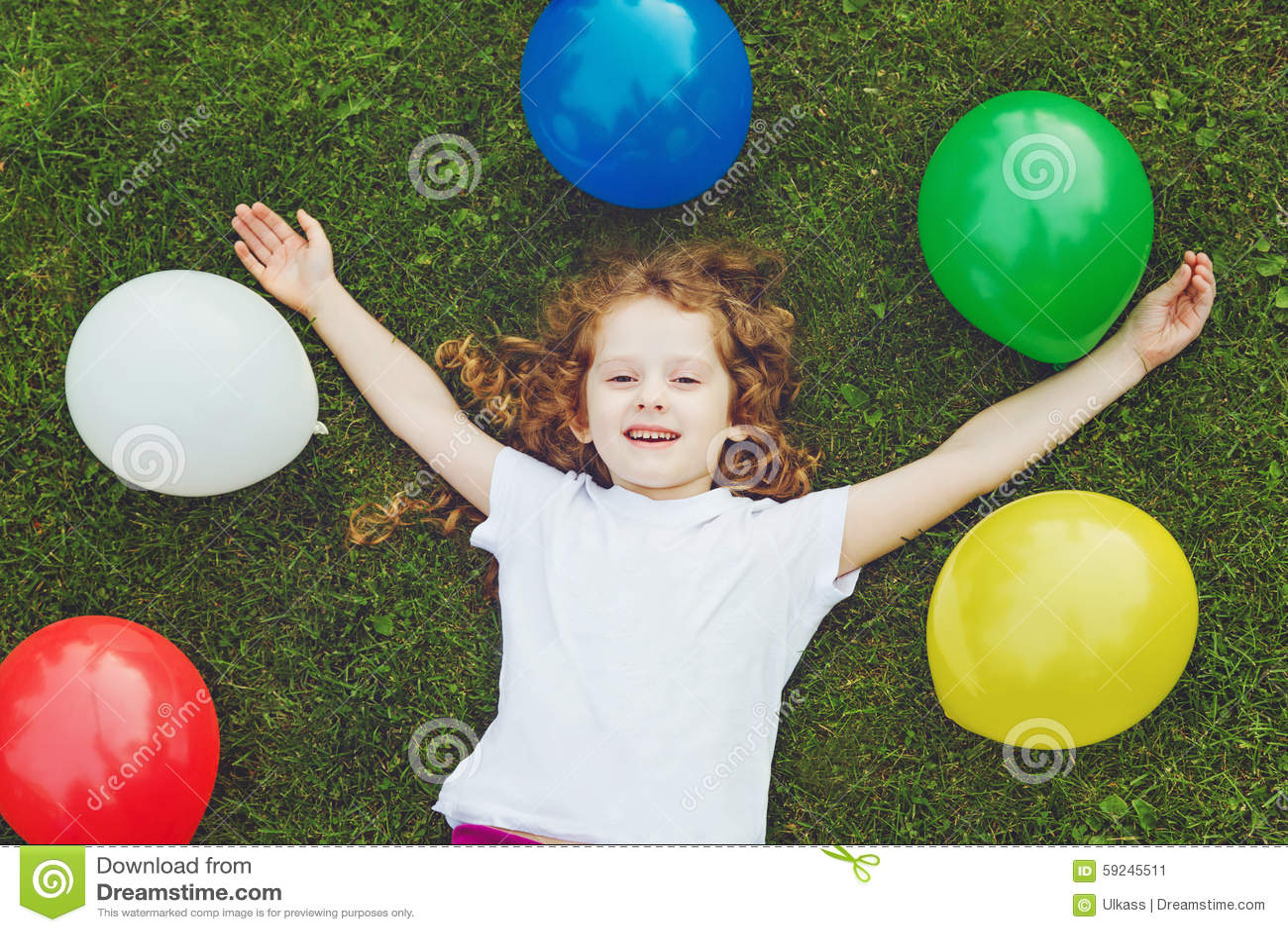 El niño feliz miente en hierba verde con los globos del arco iris en el verano