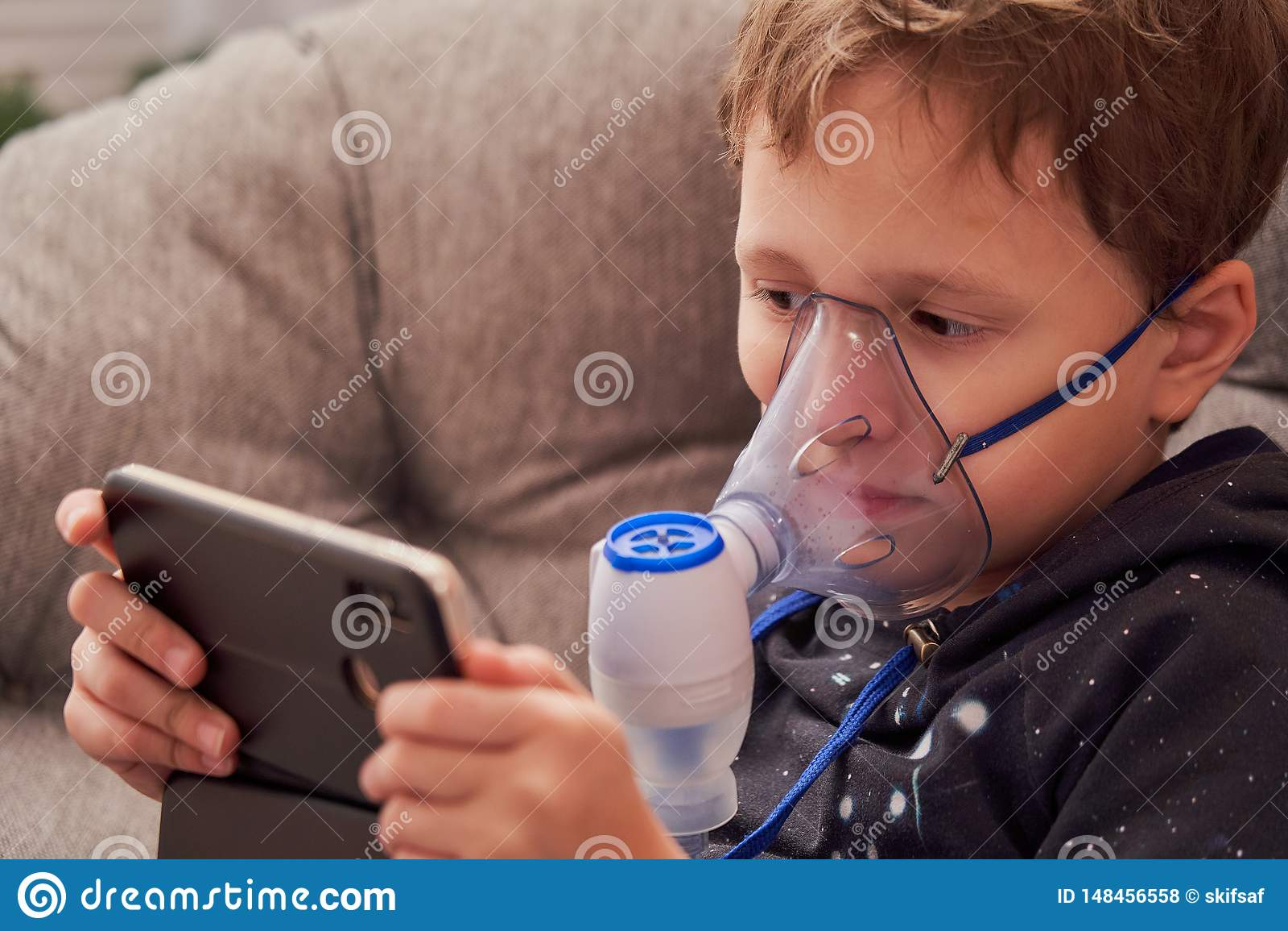 El niño hace el nebulizador de la inhalación en casa en la cara llevar un nebulizador de la máscara que inhalaba el vapor roció l