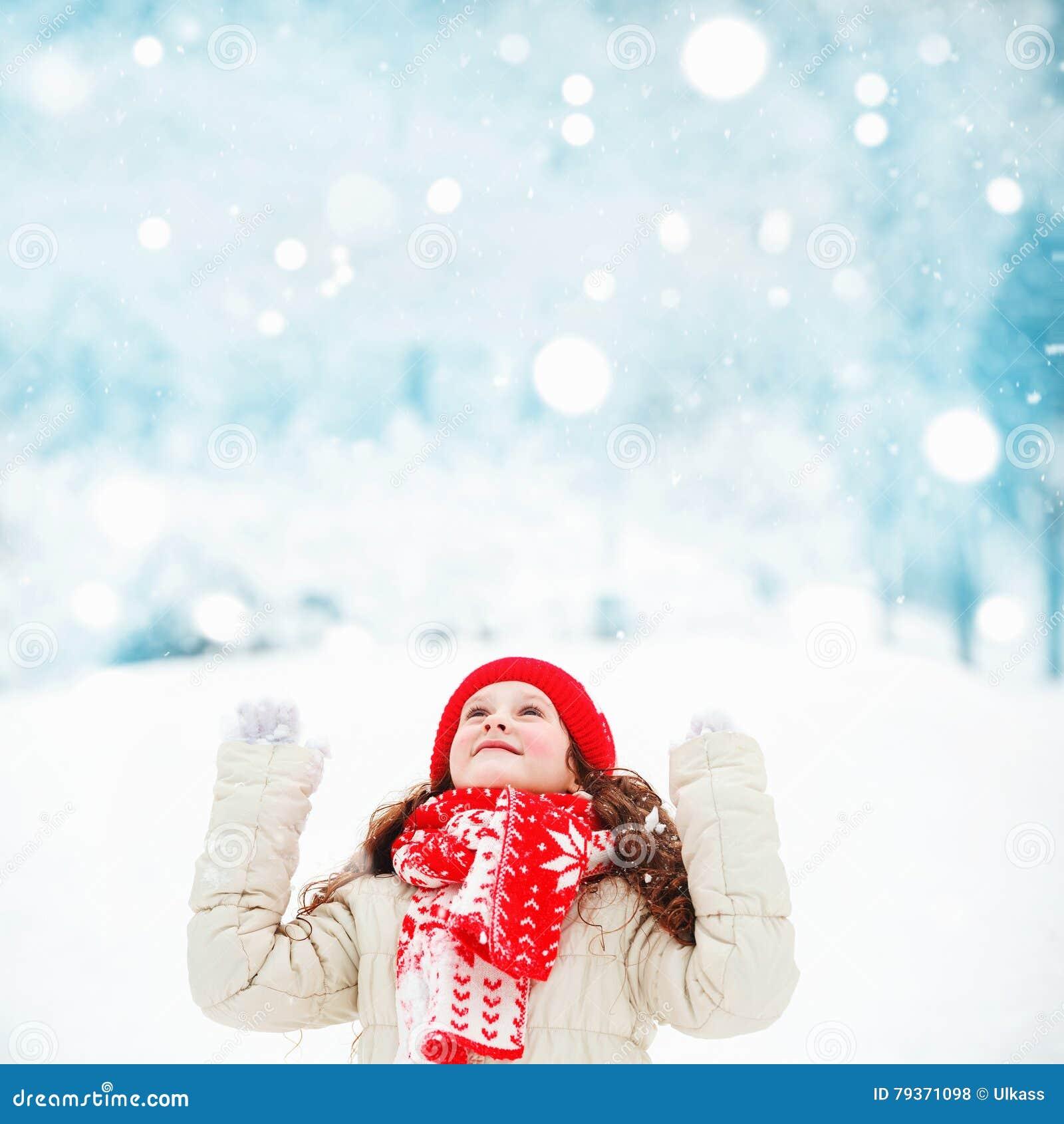 El niño hermoso estira su mano para coger los copos de nieve que caen fb1569aca4f