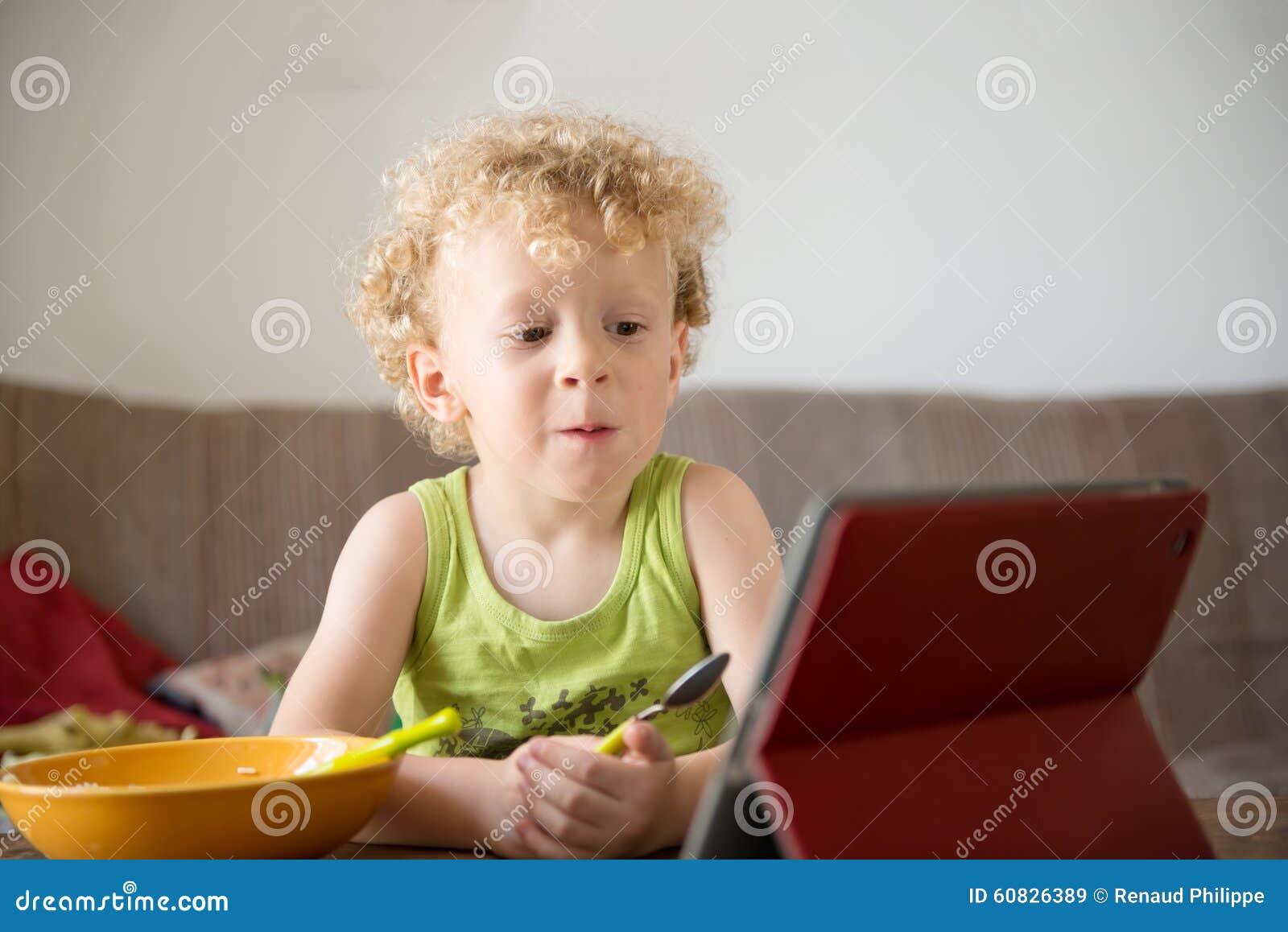 El niño joven come mientras que mira una tableta