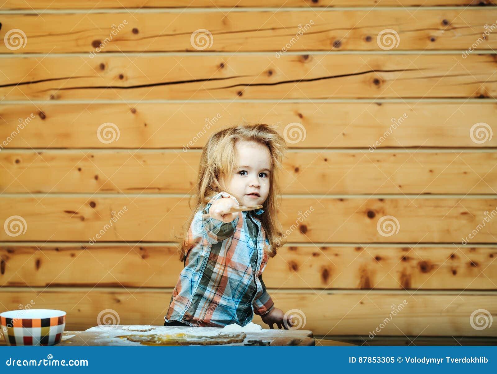 El niño lindo que cocina con la pasta, harina sostiene la pala de madera