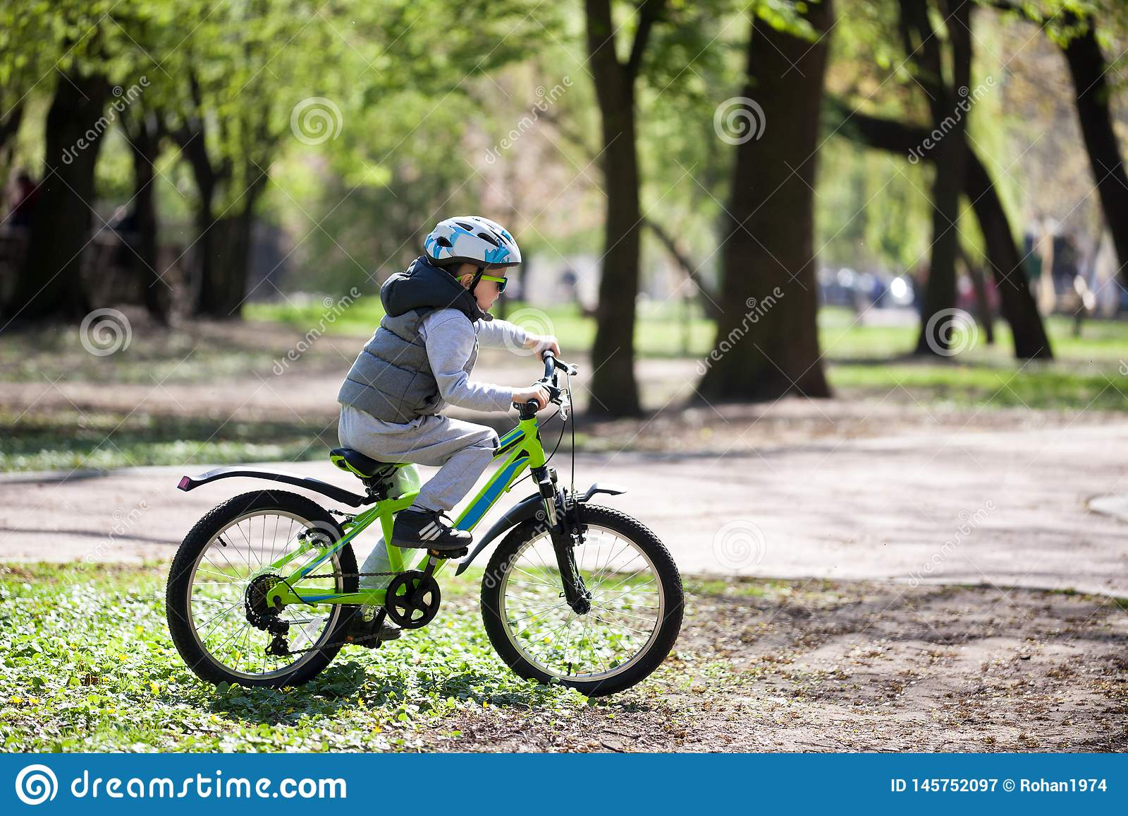 El niño pequeño aprende montar una bici en el parque El muchacho lindo en gafas de sol monta una bici Niño sonriente feliz en el