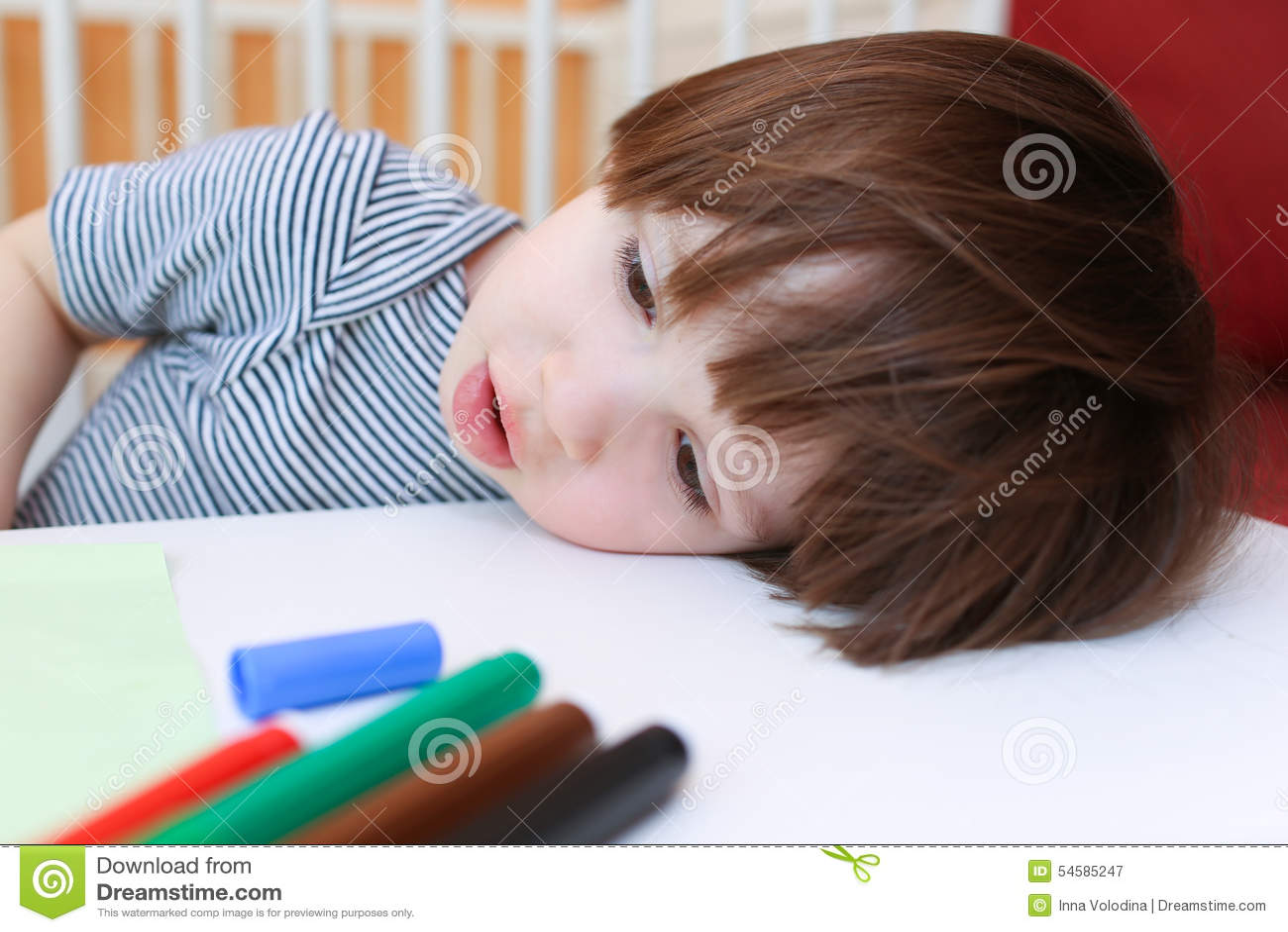 El niño pequeño cansado con fieltro encierra resto su cabeza en una tabla