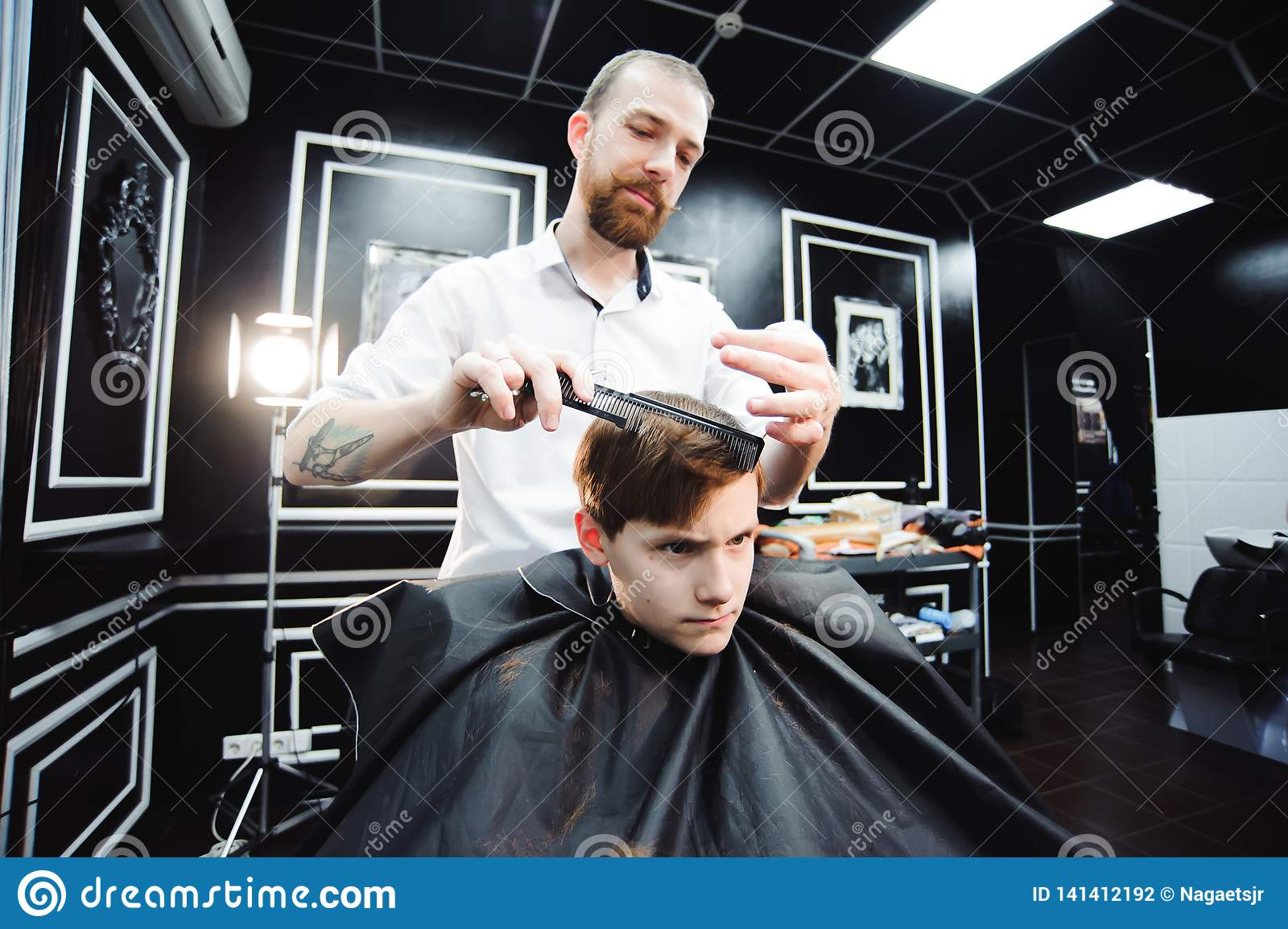 El niño pequeño lindo está consiguiendo corte de pelo del peluquero en la barbería