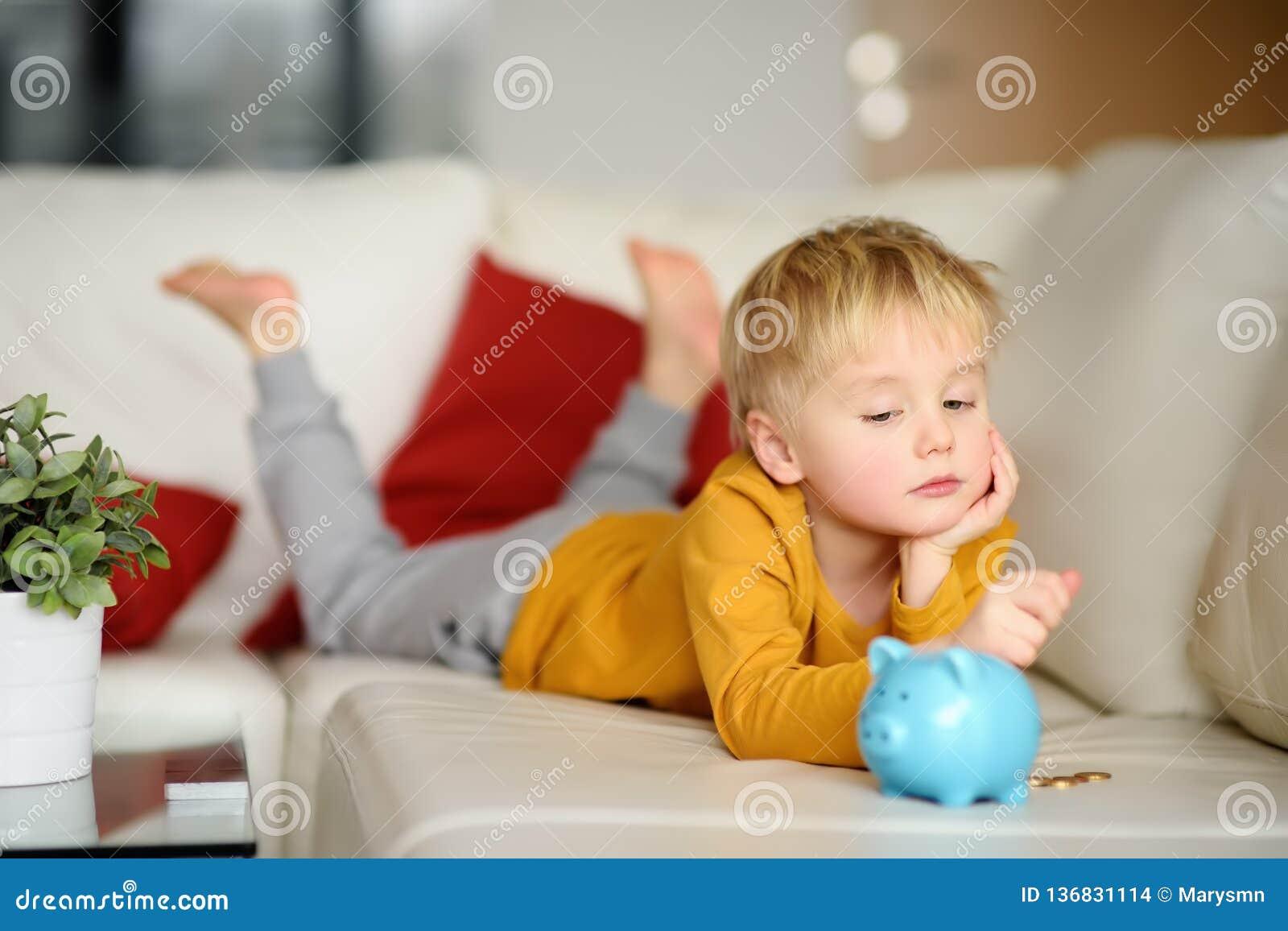 El niño pequeño mira en moneybox y planes de lo que él puede comprar