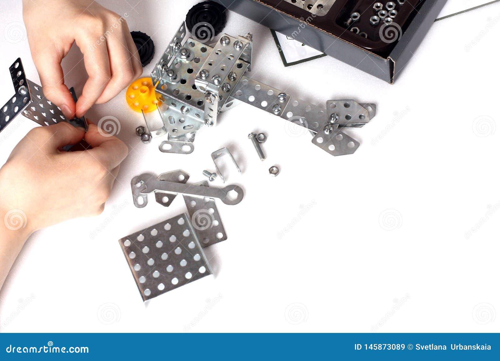 El niño recoge las piezas de metal del equipo modelo del niño