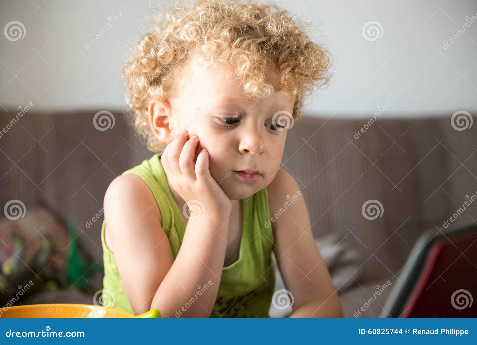 El niño rubio joven mira una tableta
