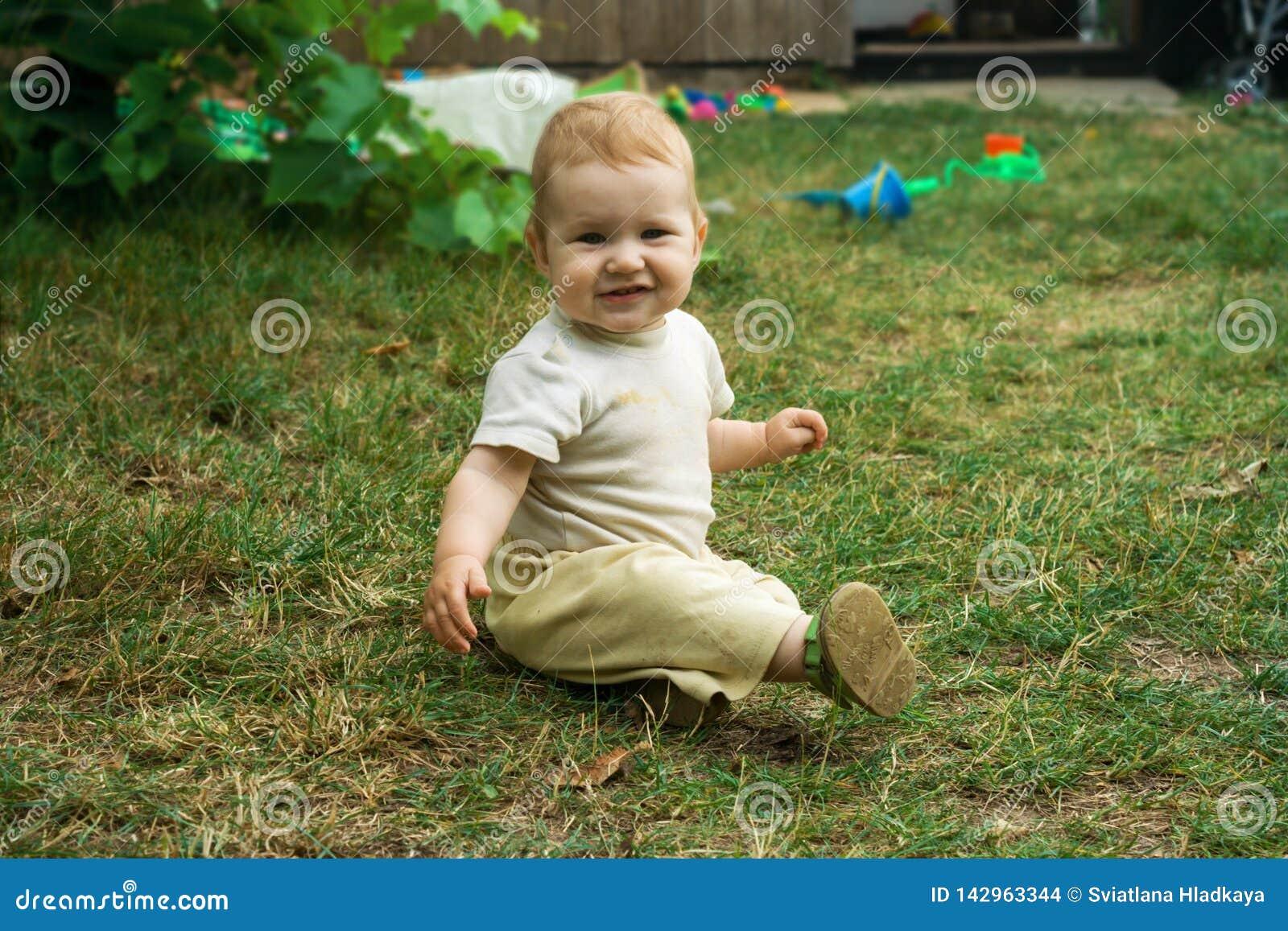 El niño se arrastra y se sienta feliz en la hierba verde Sonrisas y movimientos del niño en todos los fours alrededor de la yarda