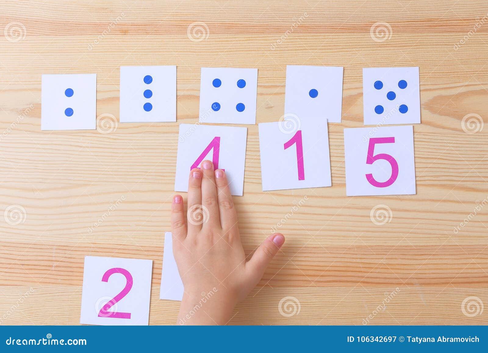 El niño separa tarjetas con números a las tarjetas con los puntos El estudio de números y de matemáticas