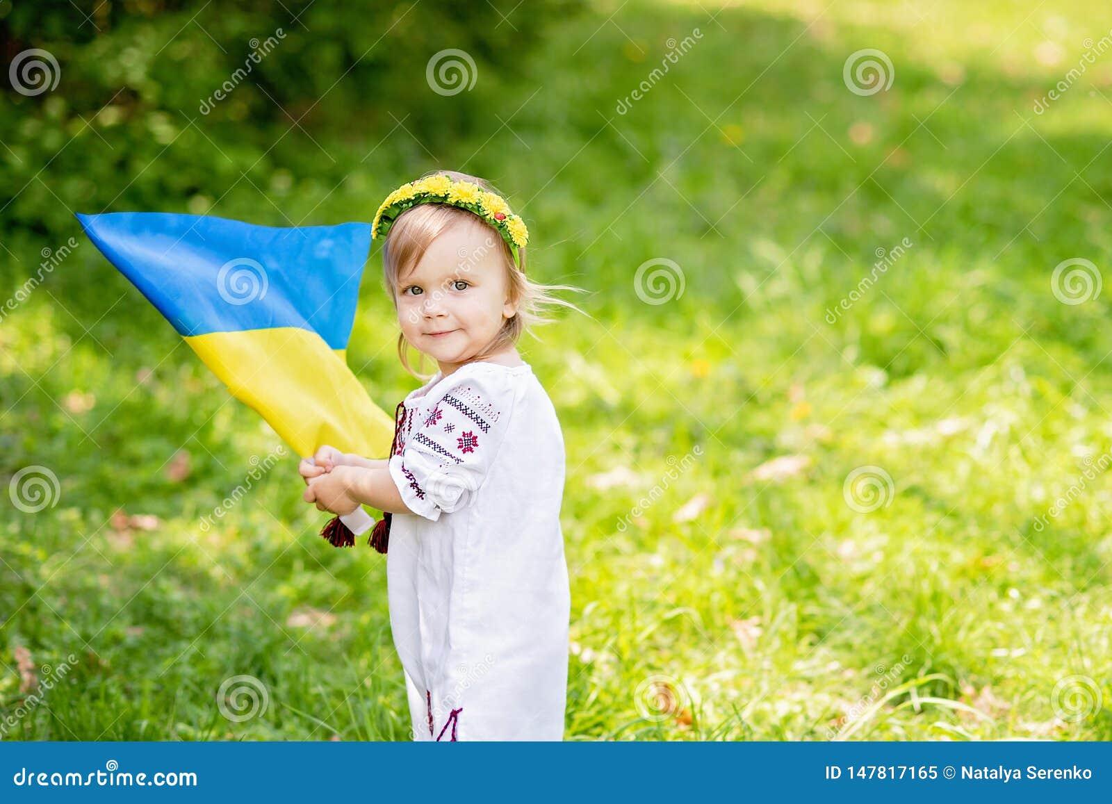 El ni?o lleva agitar bandera azul y amarilla de Ucrania en campo D?a de la Independencia del ` s de Ucrania D?a de indicador D?a