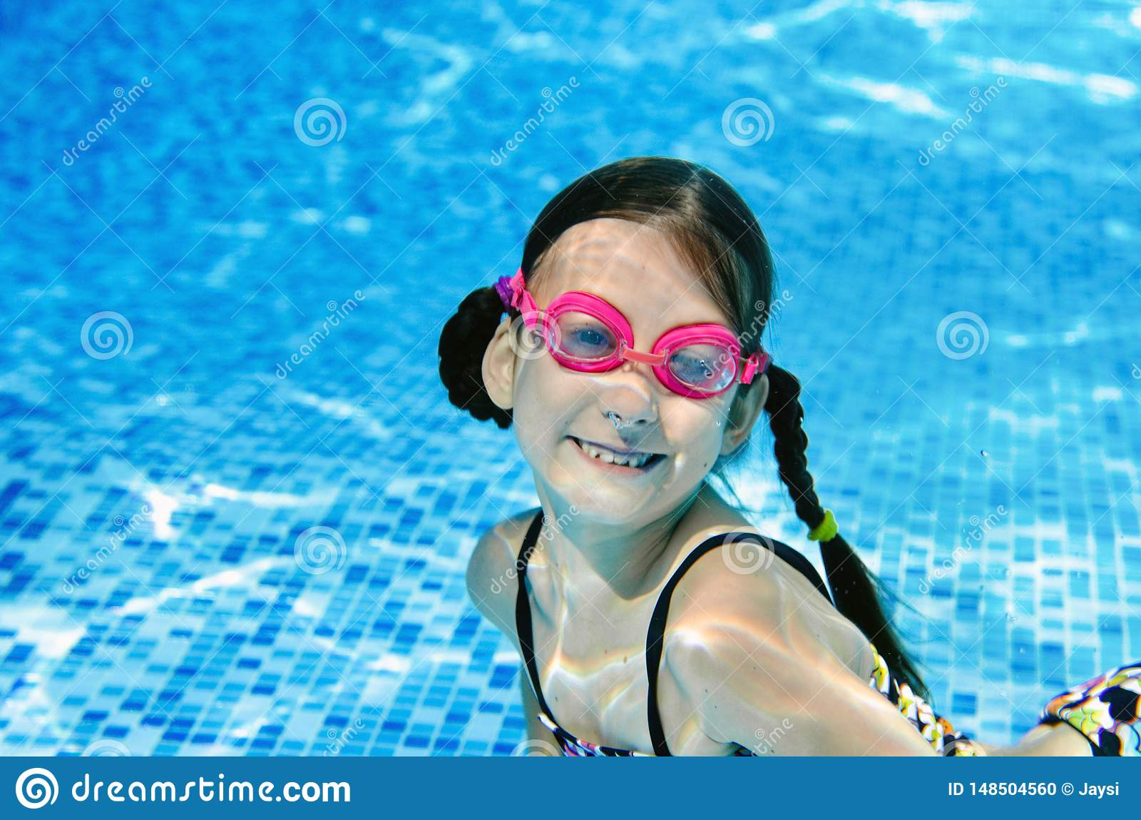 El ni?o nada bajo el agua en la piscina, zambullidas activas felices de la muchacha del adolescente y se divierte bajo el agua, l