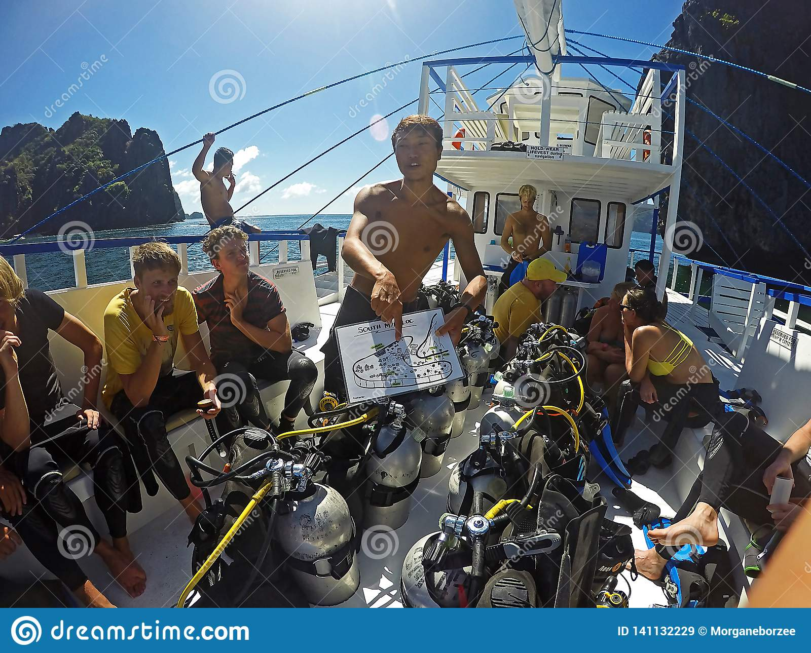 Asian dive instructor giving a dive briefing to a group of tourists