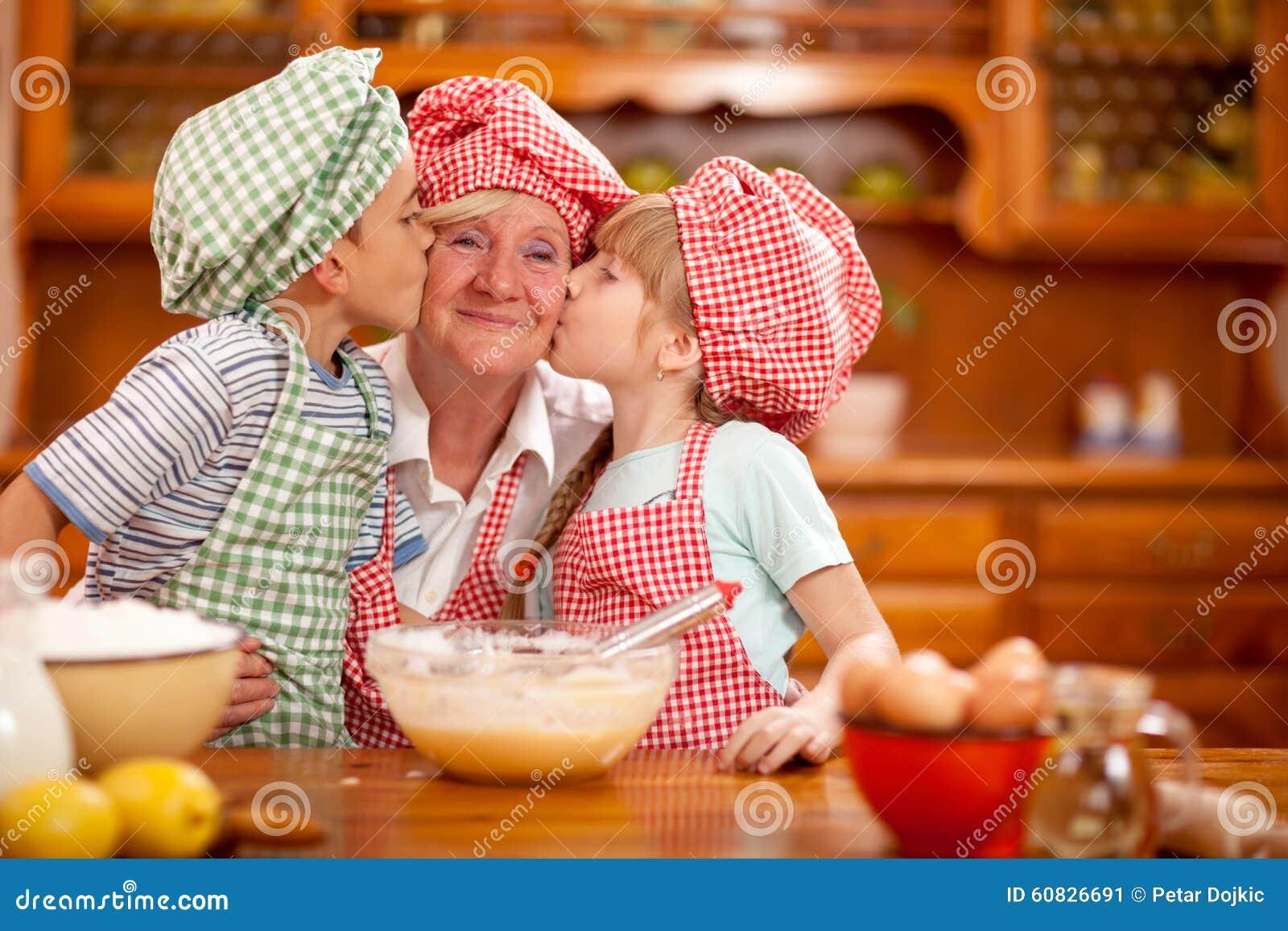 El nieto y la nieta besan a su abuela en la cocina