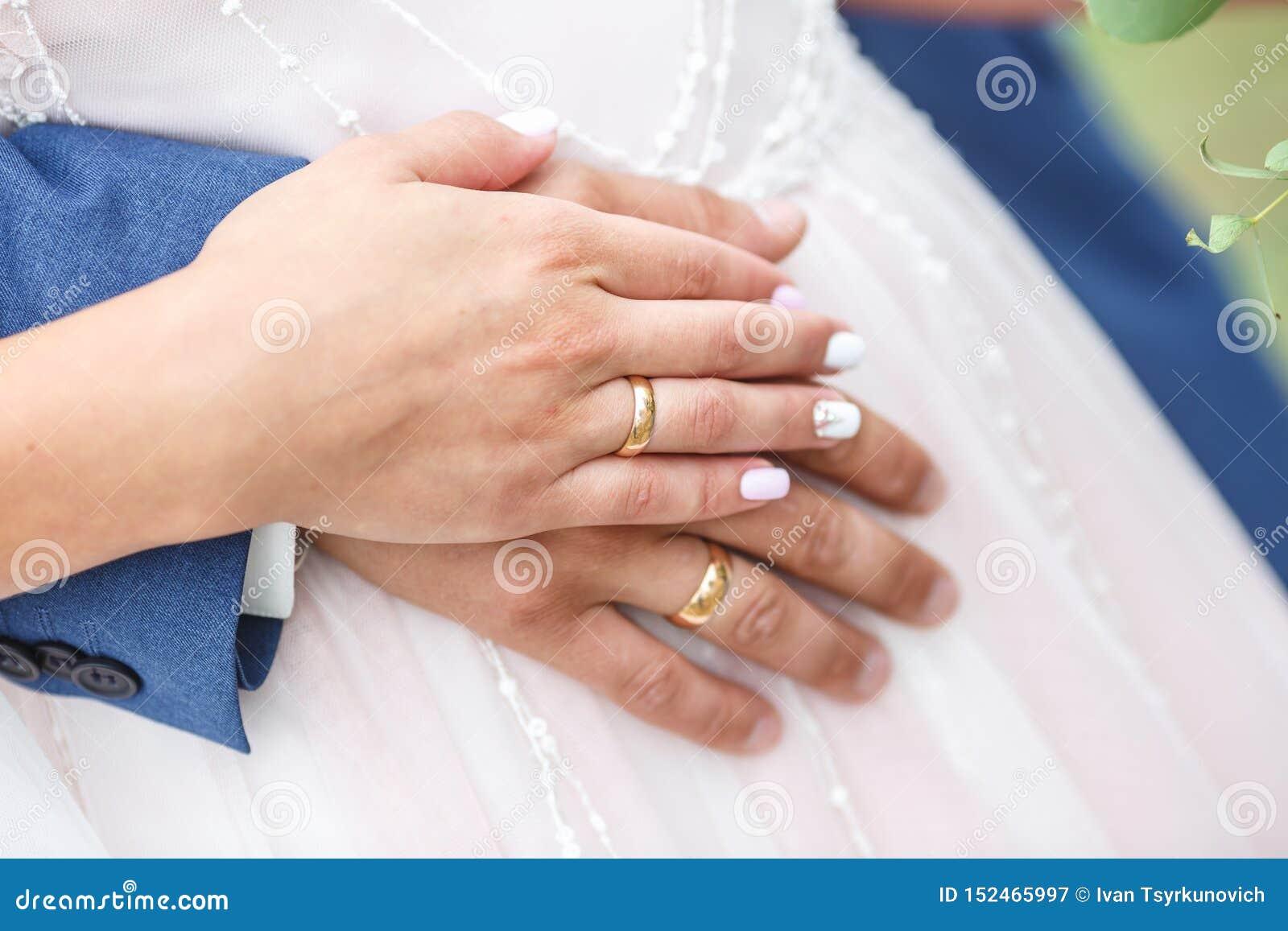 El novio abraza a la novia anillos en las manos de pares nuevo-casados