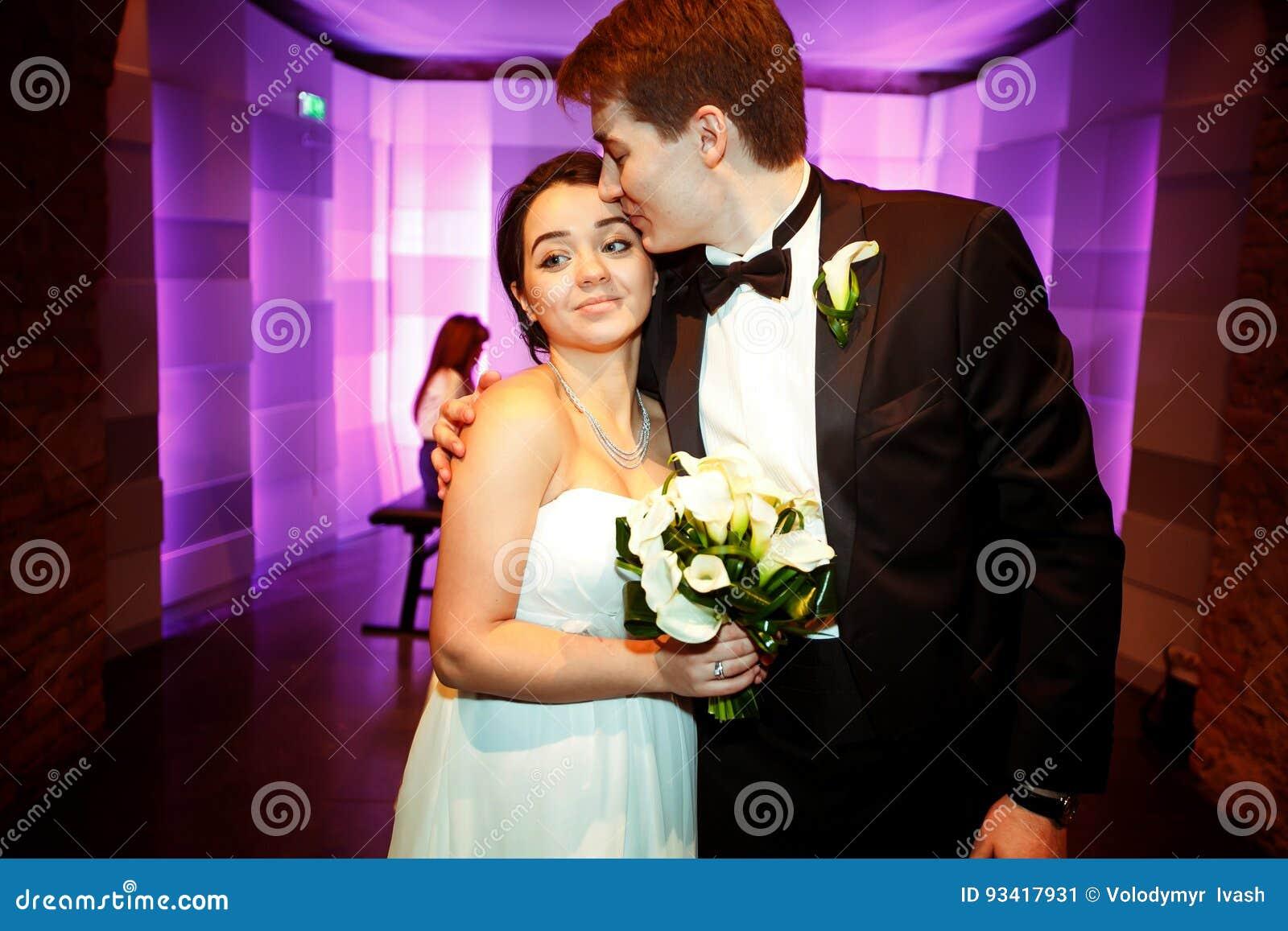 El novio abraza a una novia blanda que se coloca con ella en un restaurante