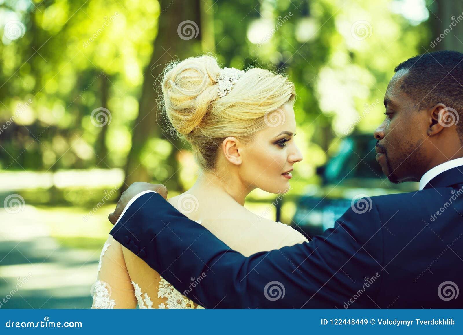 El novio cariñoso toca el hombro de la novia adorable