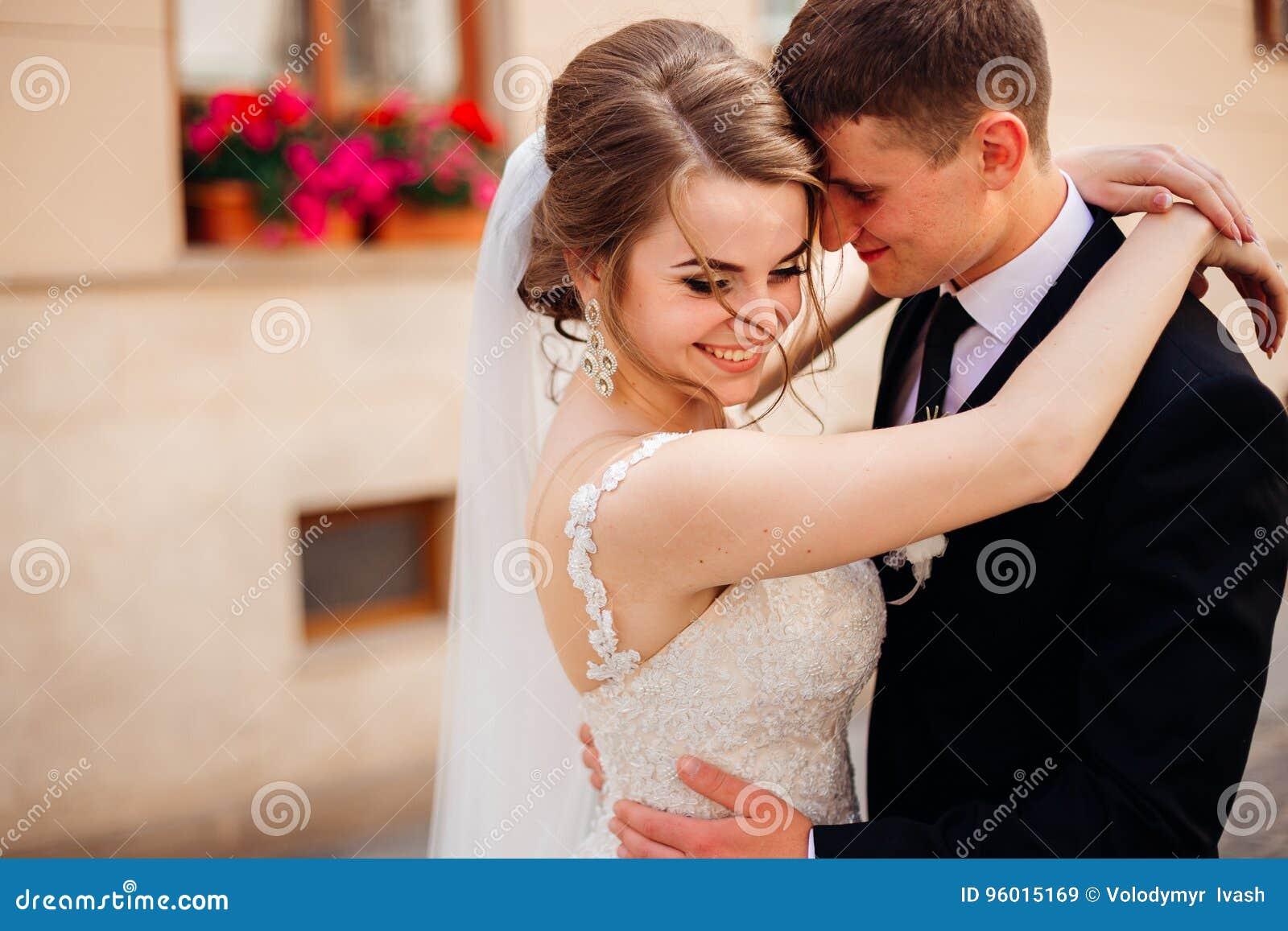 El novio detiene a la novia hermosa en sus brazos