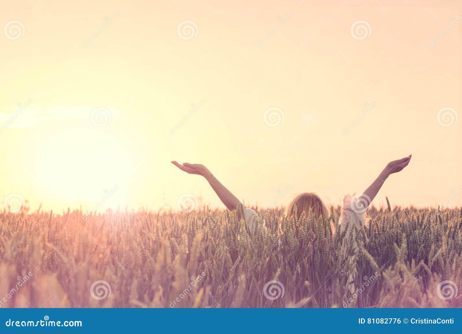 El nuevo día agradable, mujer con los brazos aumentados abraza el sol