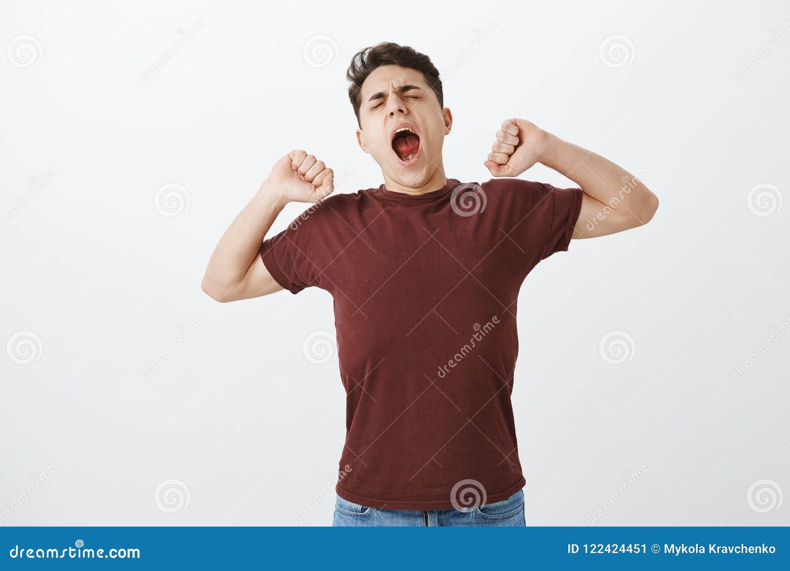 El odio despierta temprano Individuo hermoso de bostezo soñoliento en camisa roja, stratching y cabeza inclinable con los ojos ce