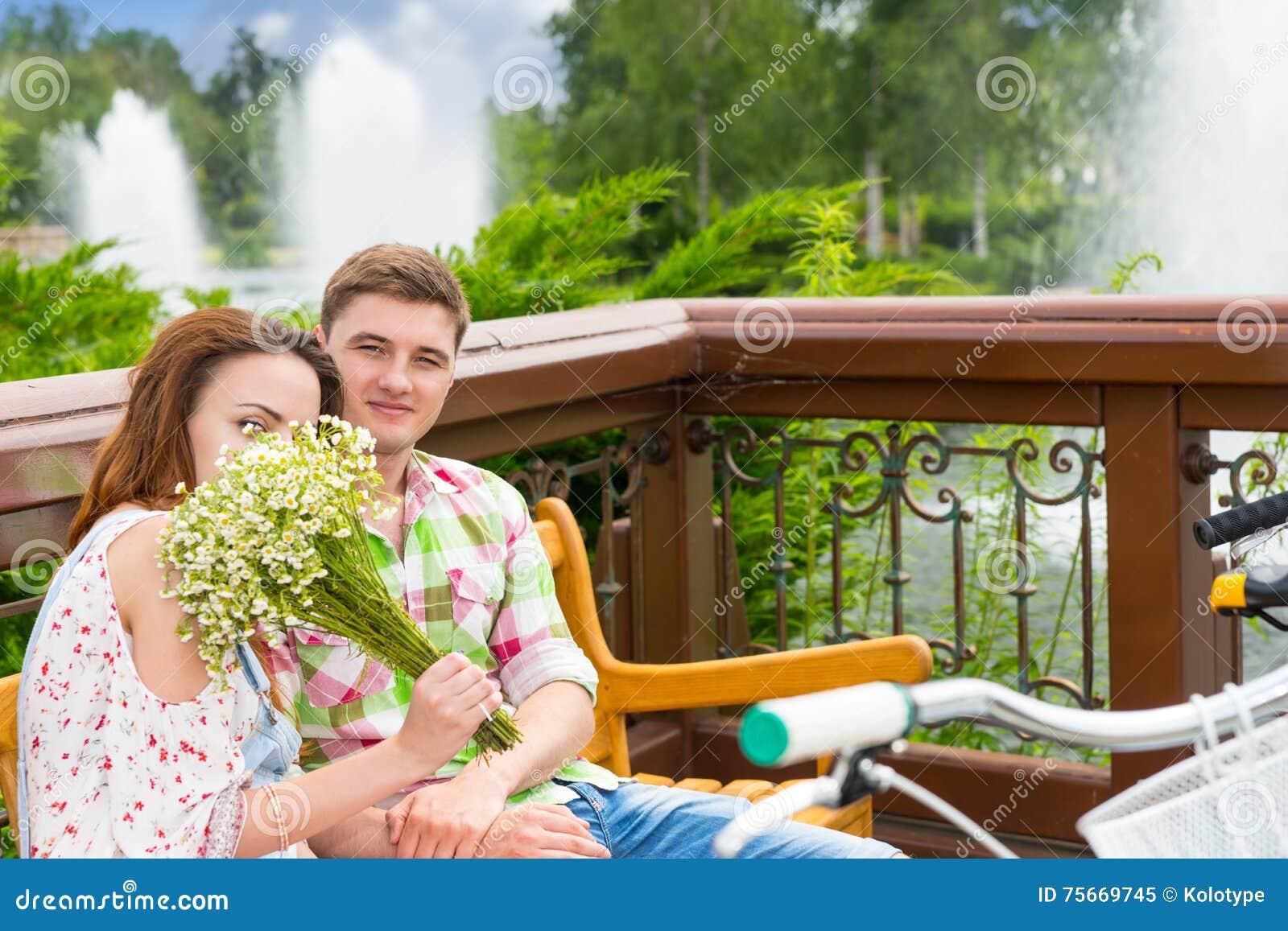 El oler femenino de Youg florece mientras que se sienta en un banco con un muchacho