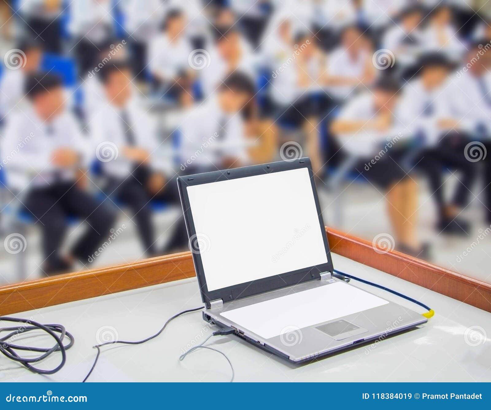 El ordenador en los estudiantes de la tabla y del grupo empaña sentarse en una sala de clase