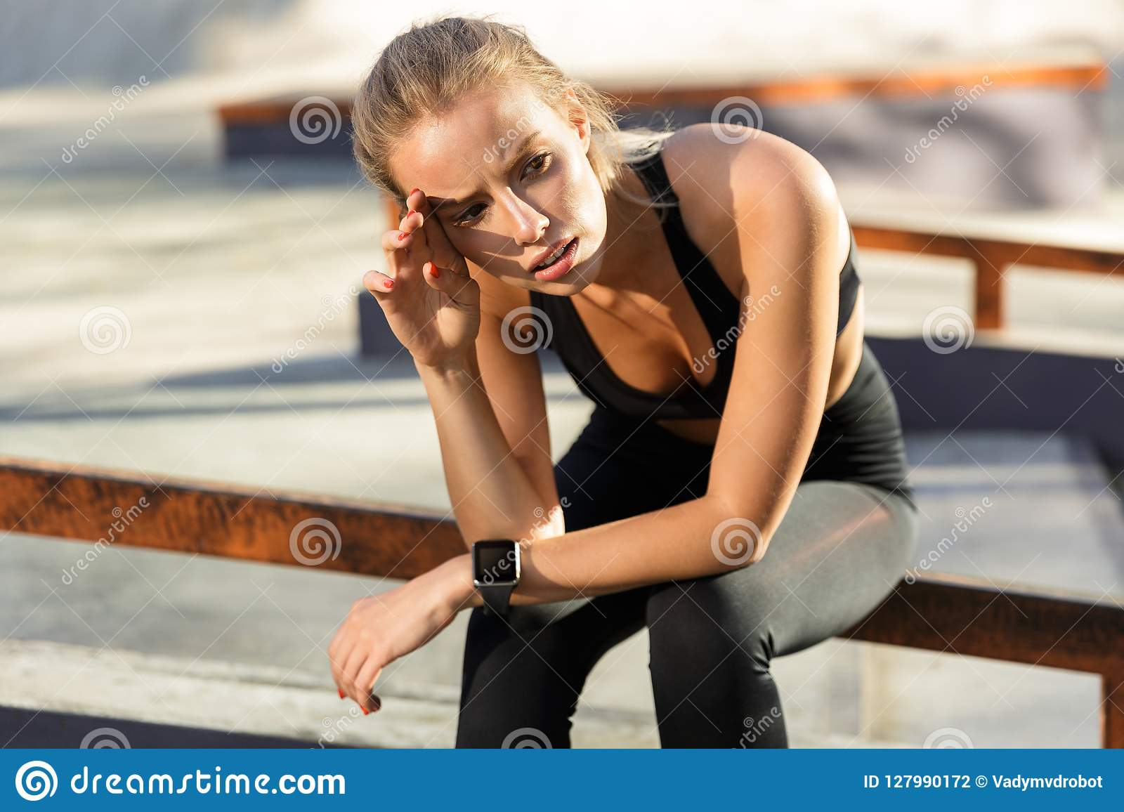 El oung agujereado cansado se divierte a la mujer que sienta al aire libre la mirada a un lado