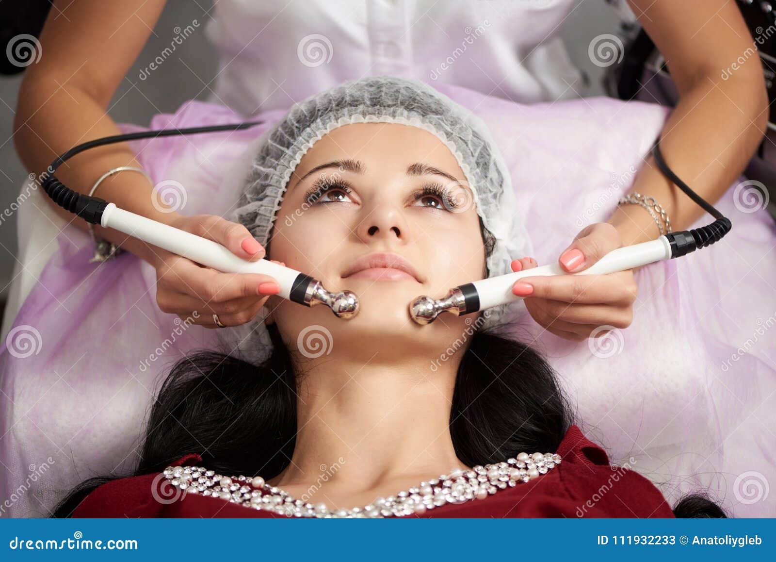 El paciente femenino está teniendo masaje facial en un salón de belleza Cosmetología y rutina del cuidado de piel