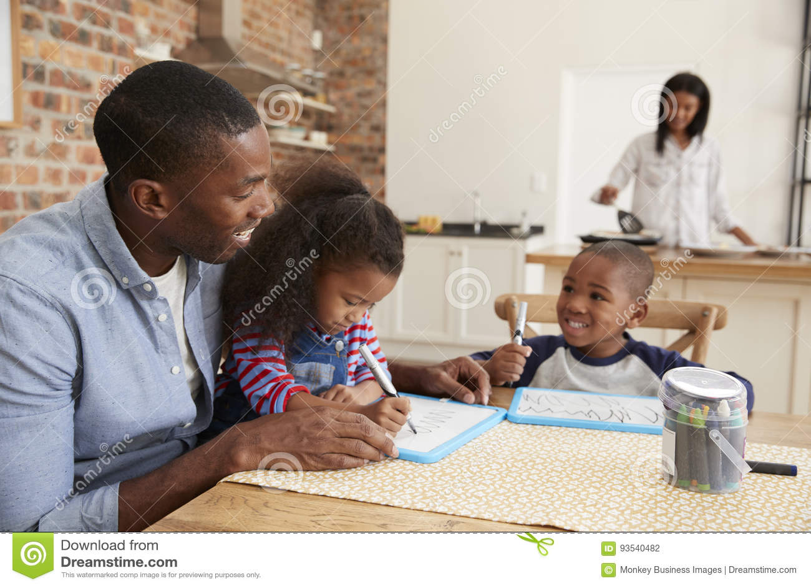 El padre And Children Drawing en la tabla como madre prepara la comida