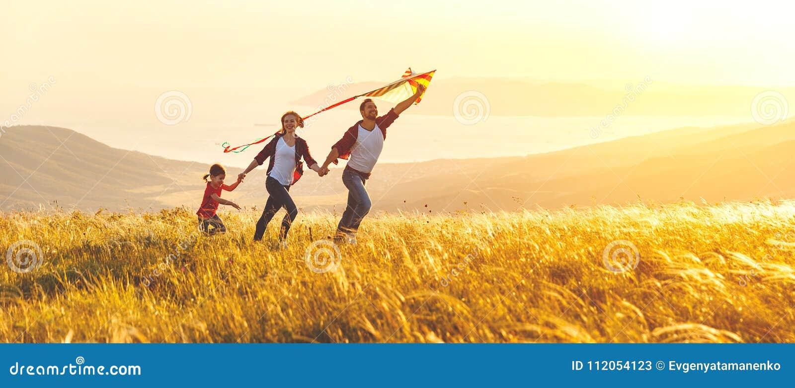 El padre de la familia, la madre y la hija felices del niño lanzan una cometa encendido
