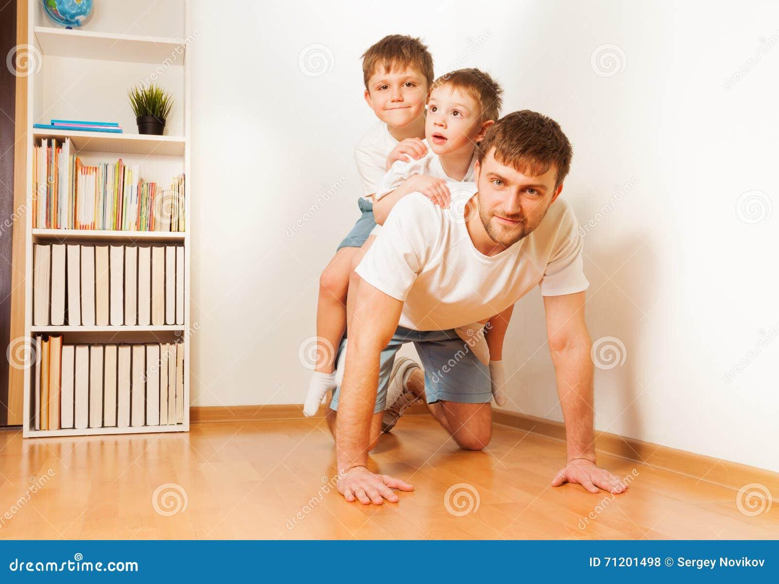 El padre que da a sus dos hijos lleva a cuestas paseo
