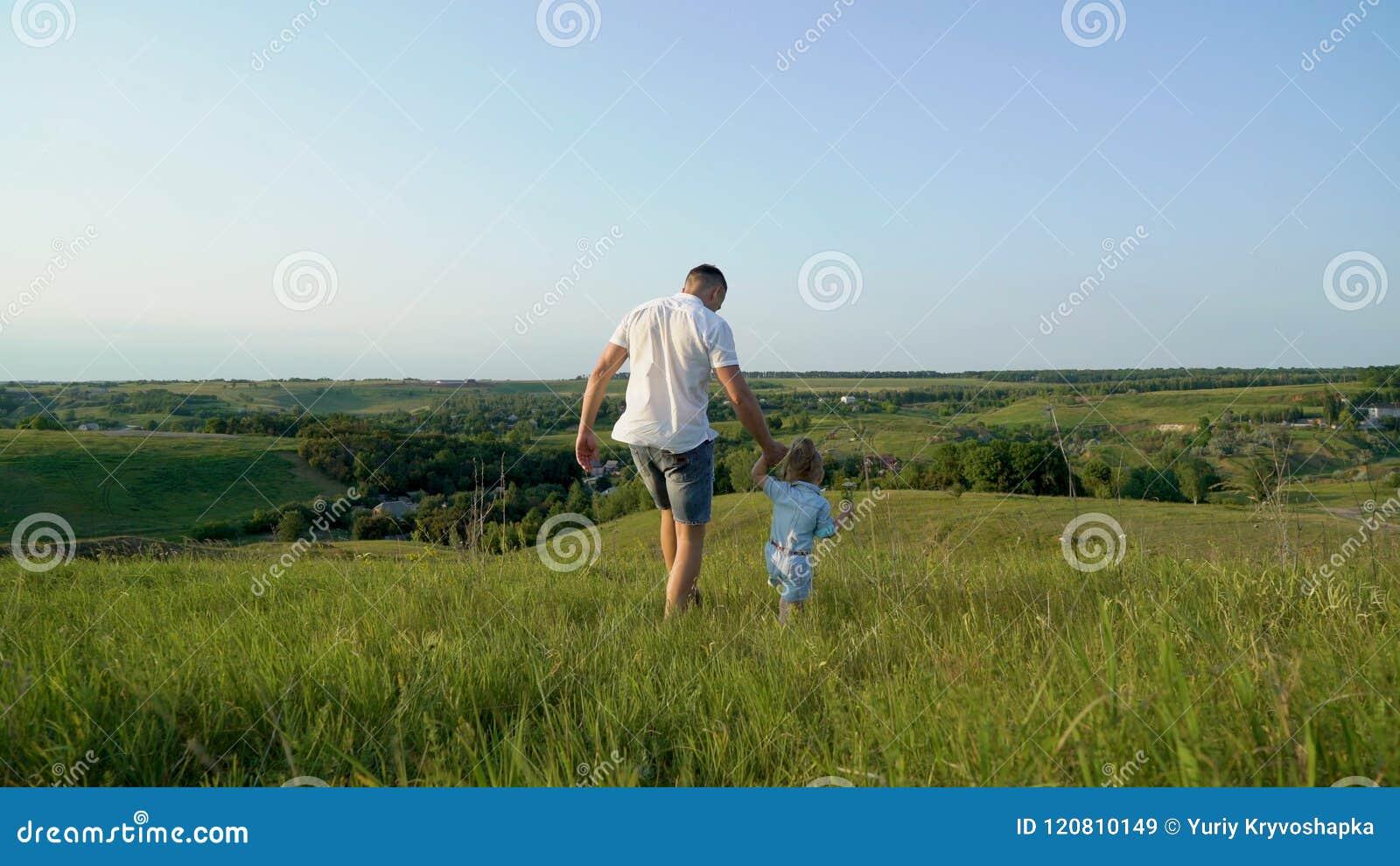 El padre y la hija comparten el amor que lleva a cabo las manos que caminan juntos en alto campo de hierba