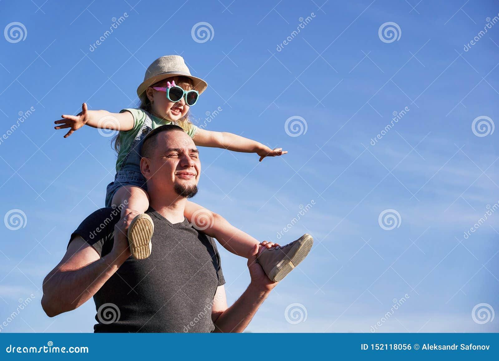 El padre y la hija en hombros disfrutan feliz papá que detiene a poca hija que sienta en imitadores el vuelo del papa