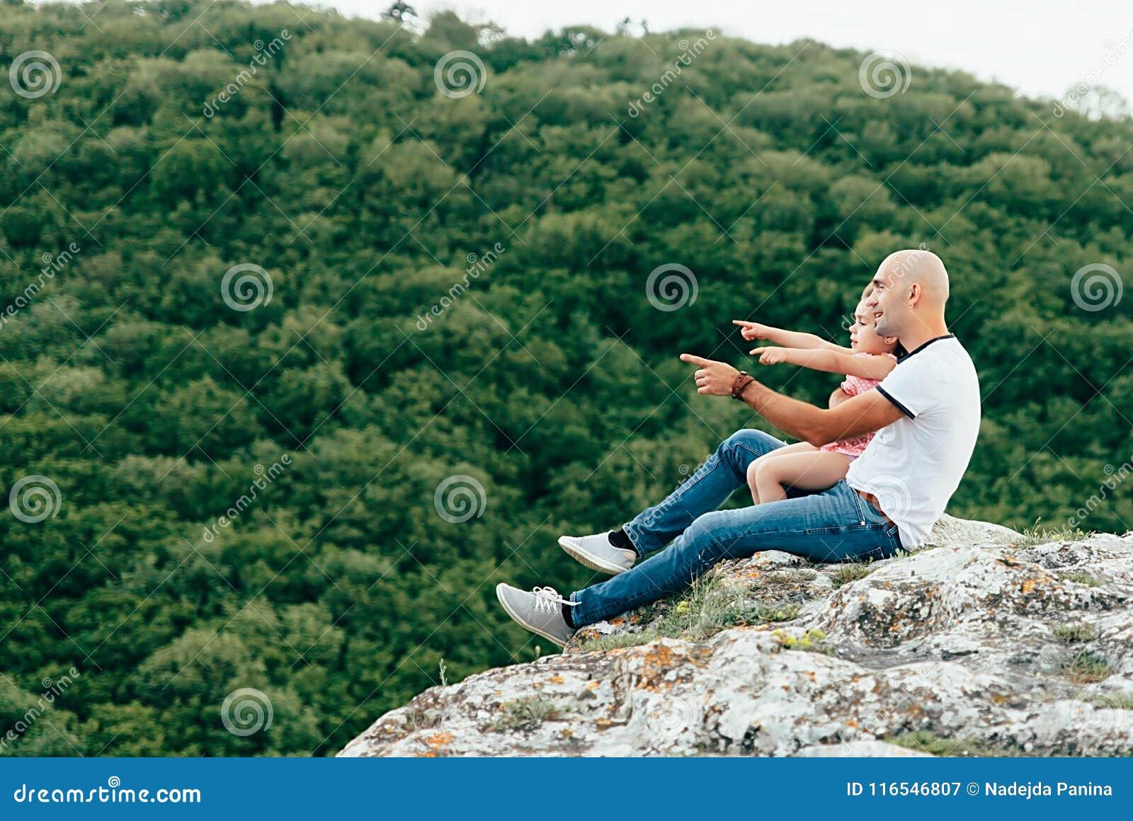 El padre y la hija que se sientan en la montaña oscilan