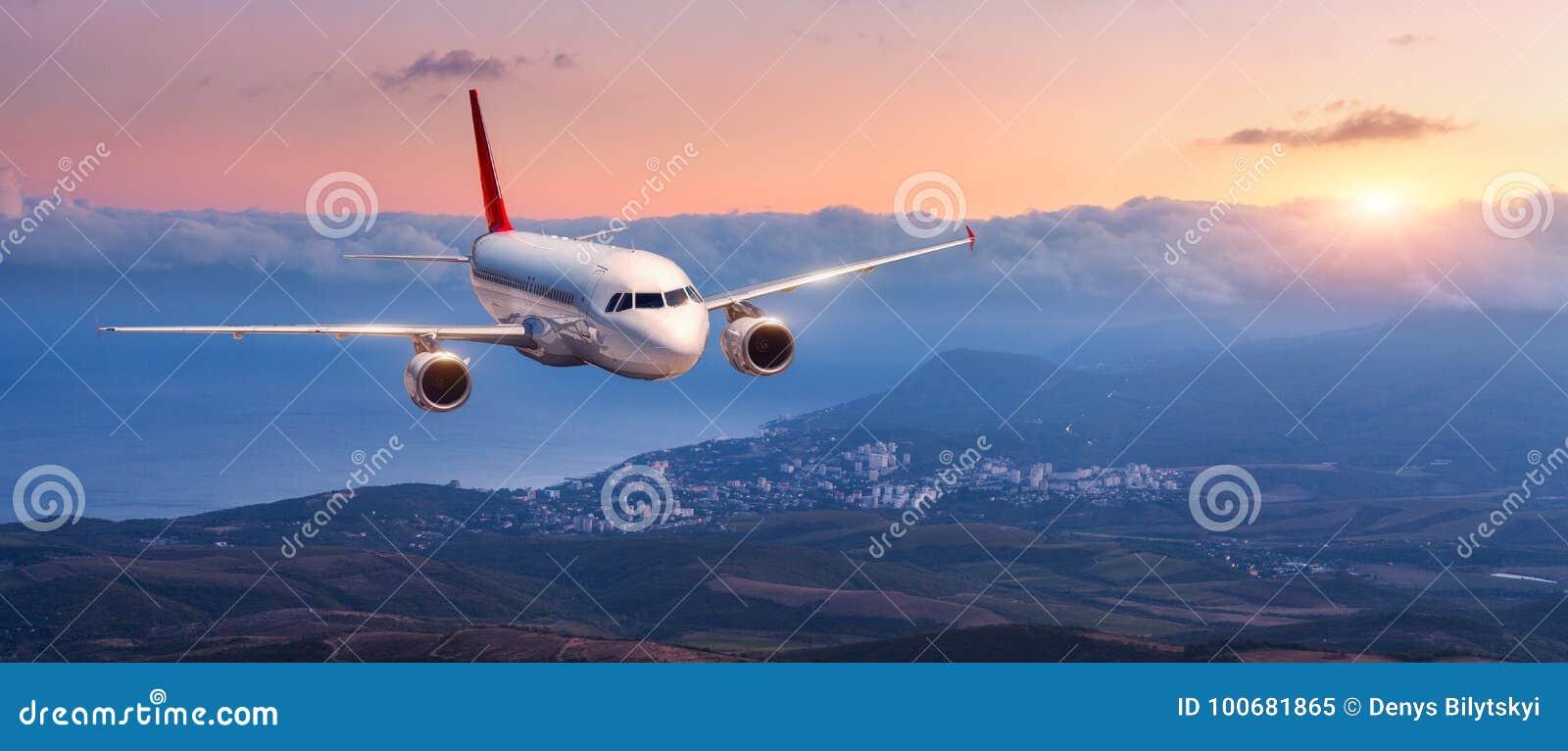 El paisaje con el aeroplano blanco está volando en el cielo anaranjado