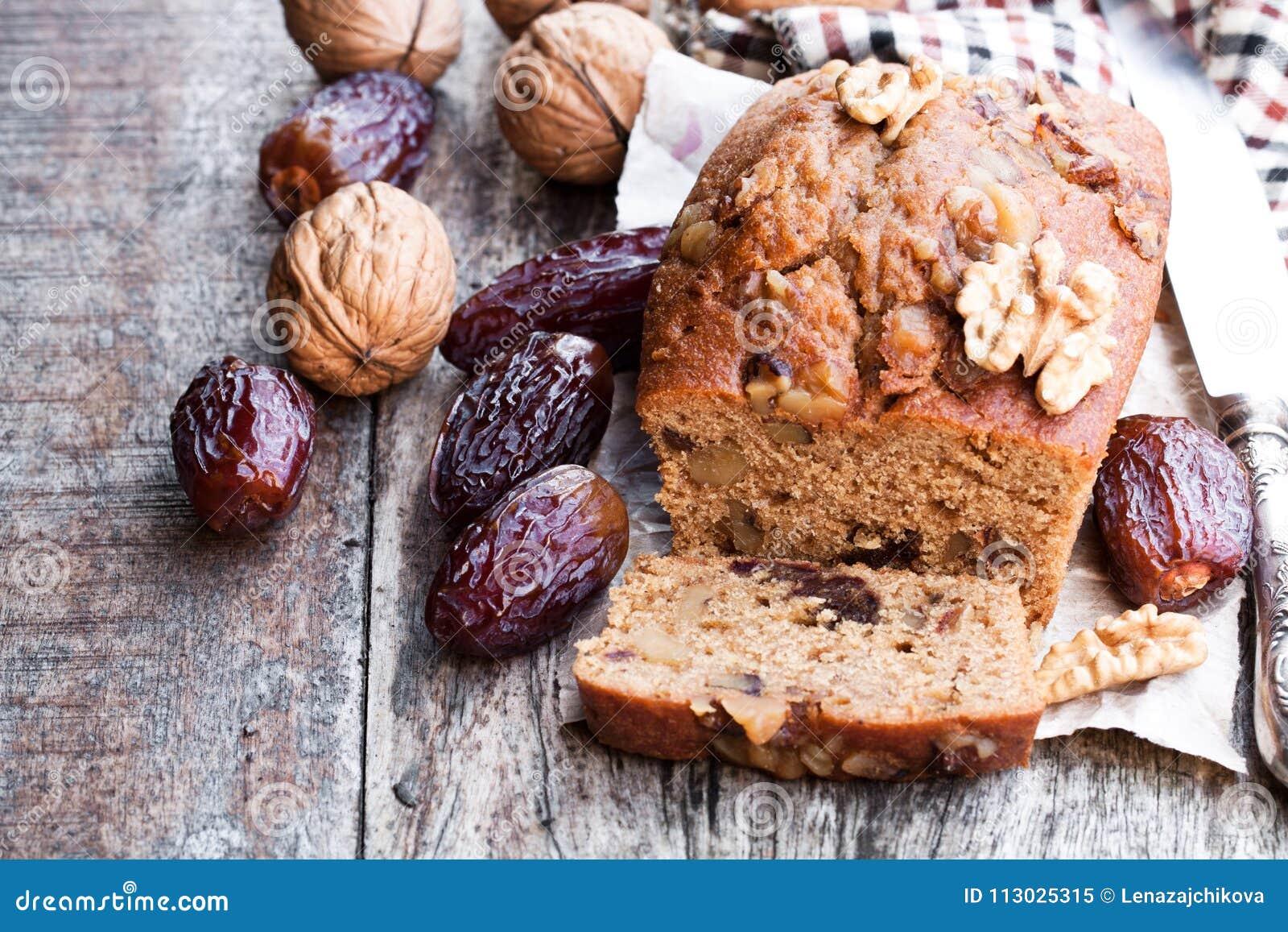 El pan hecho en casa de la fecha y de la nuez se apelmaza en la tabla de madera vieja