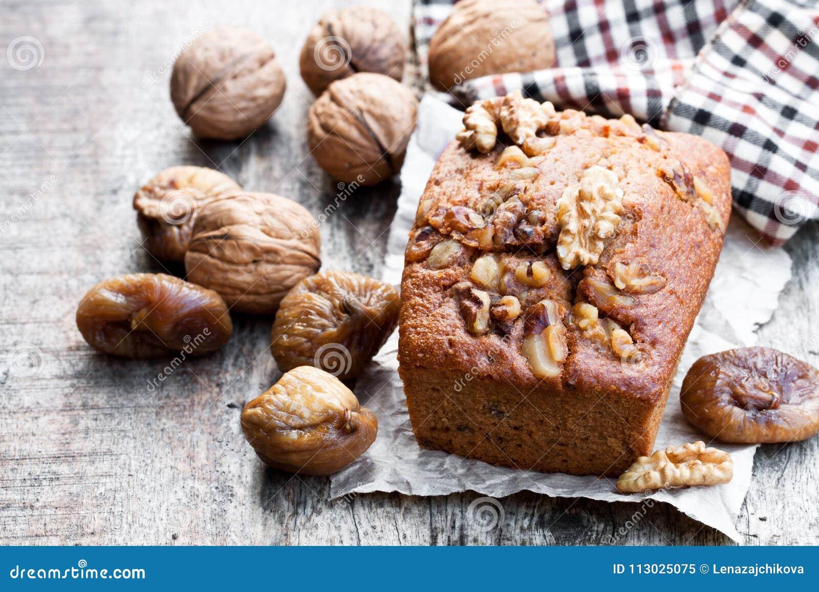 El pan hecho en casa del higo y de la nuez se apelmaza en la tabla de madera vieja